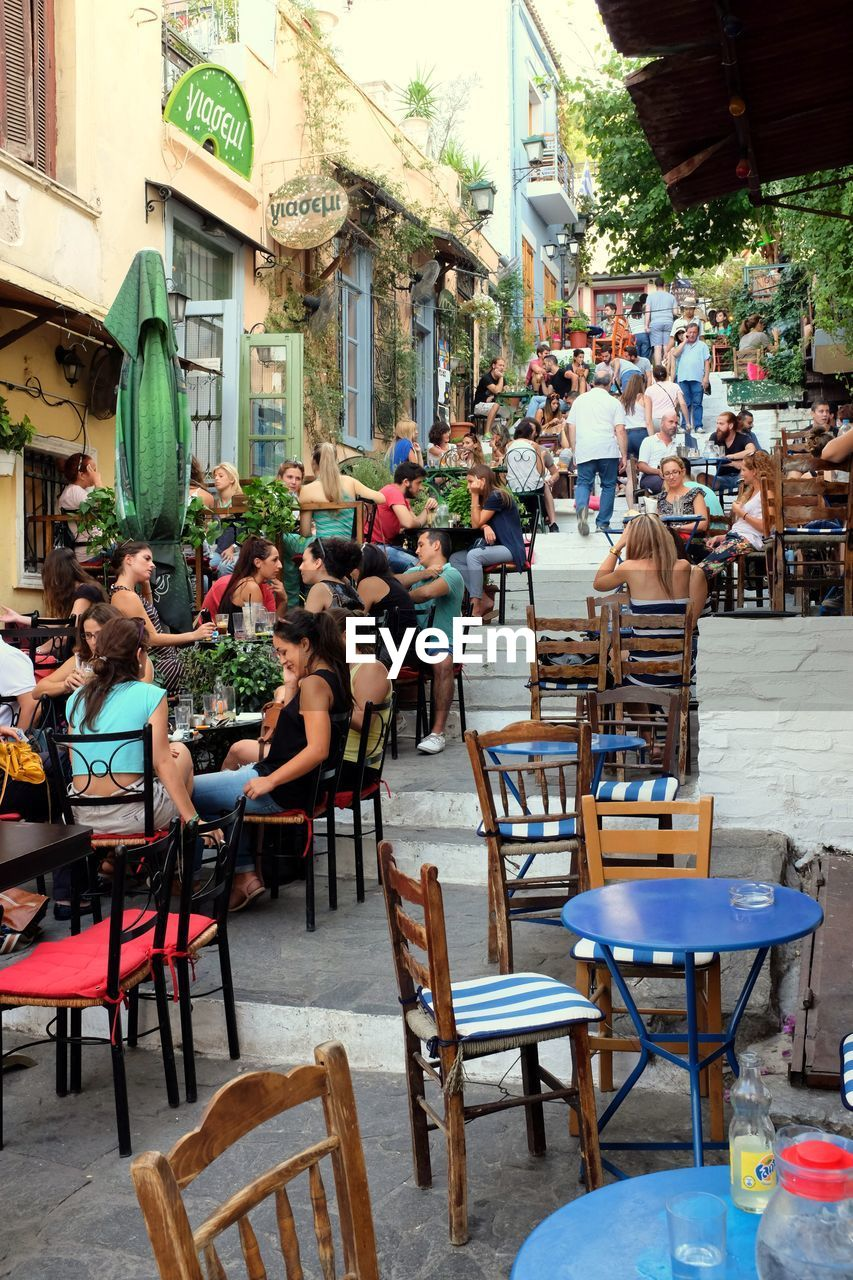 table, chair, restaurant, cafe, sidewalk cafe, outdoor cafe, sitting, large group of people, women, day, outdoors, real people, architecture, men, building exterior, relaxation, togetherness, city, adult, people