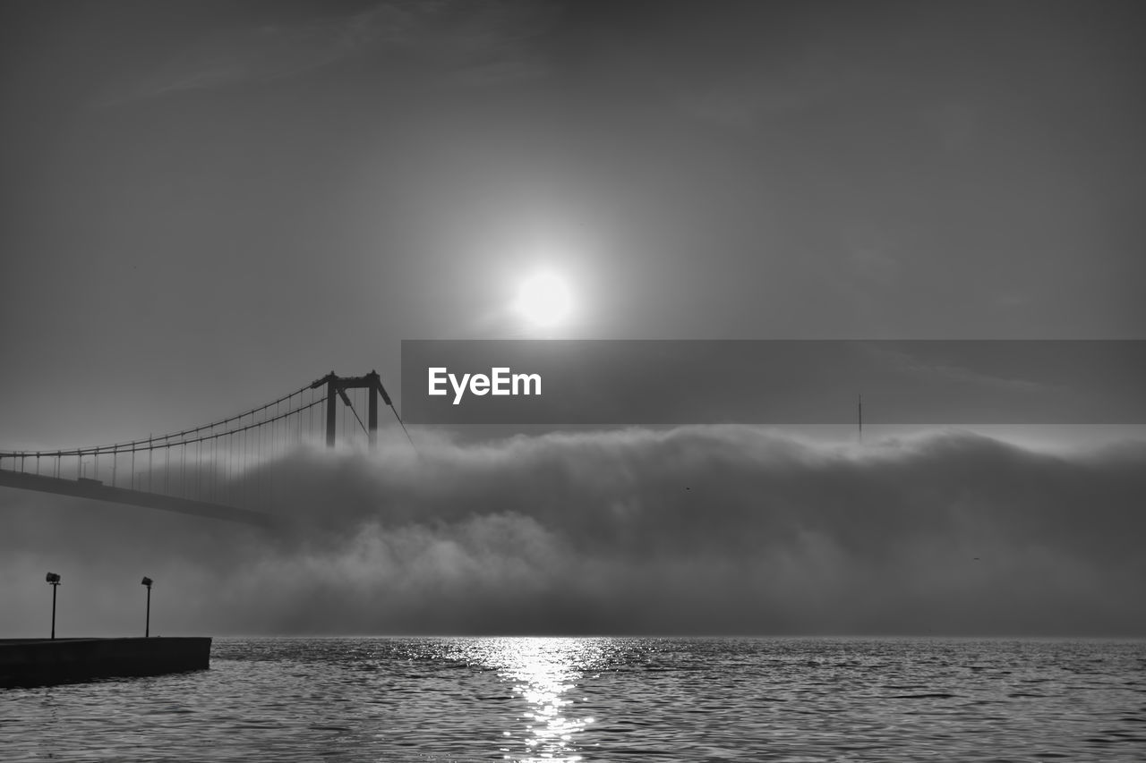 Silhouette bridge over sea against sky and fog