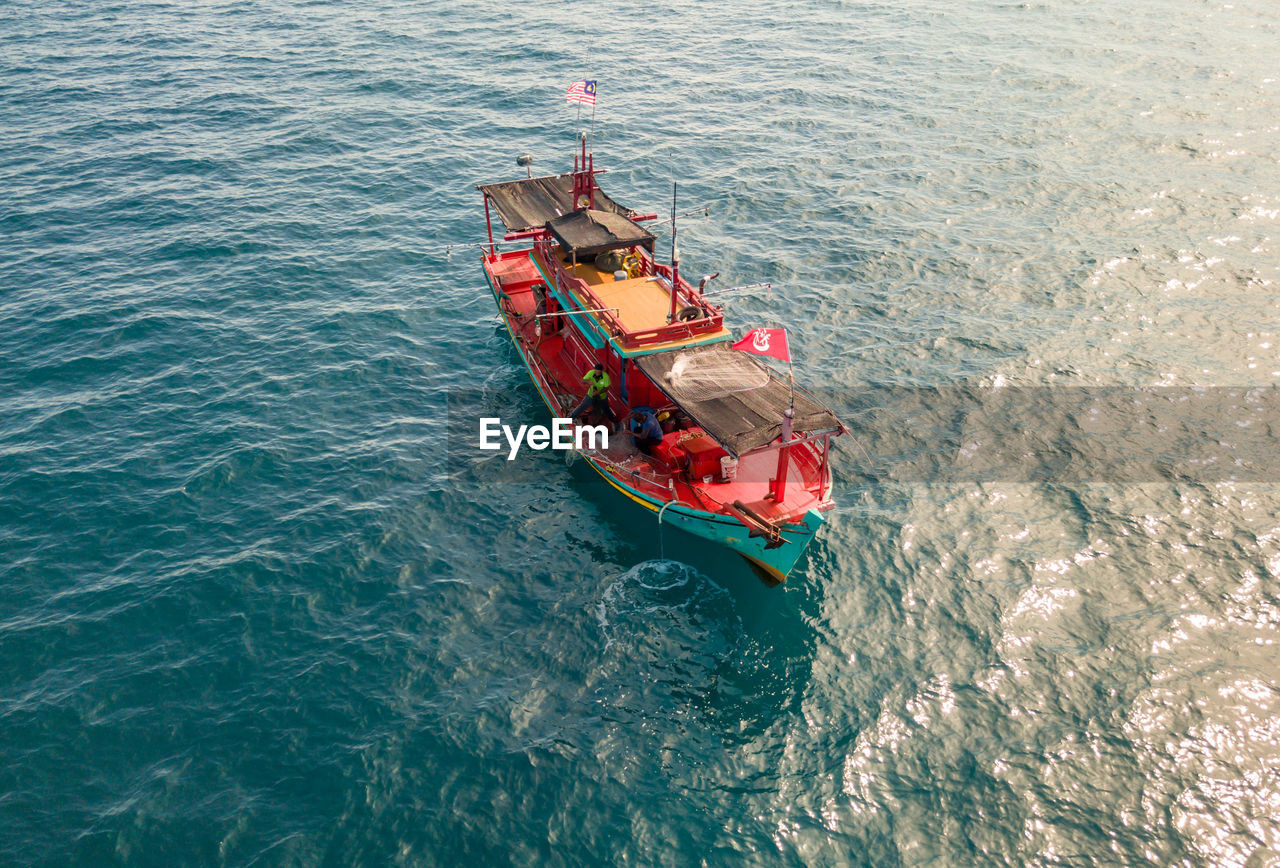 high angle view, nautical vessel, mode of transportation, transportation, water, sea, nature, day, waterfront, no people, outdoors, beauty in nature, travel, motion, ship, scenics - nature, sailing, red, turquoise colored