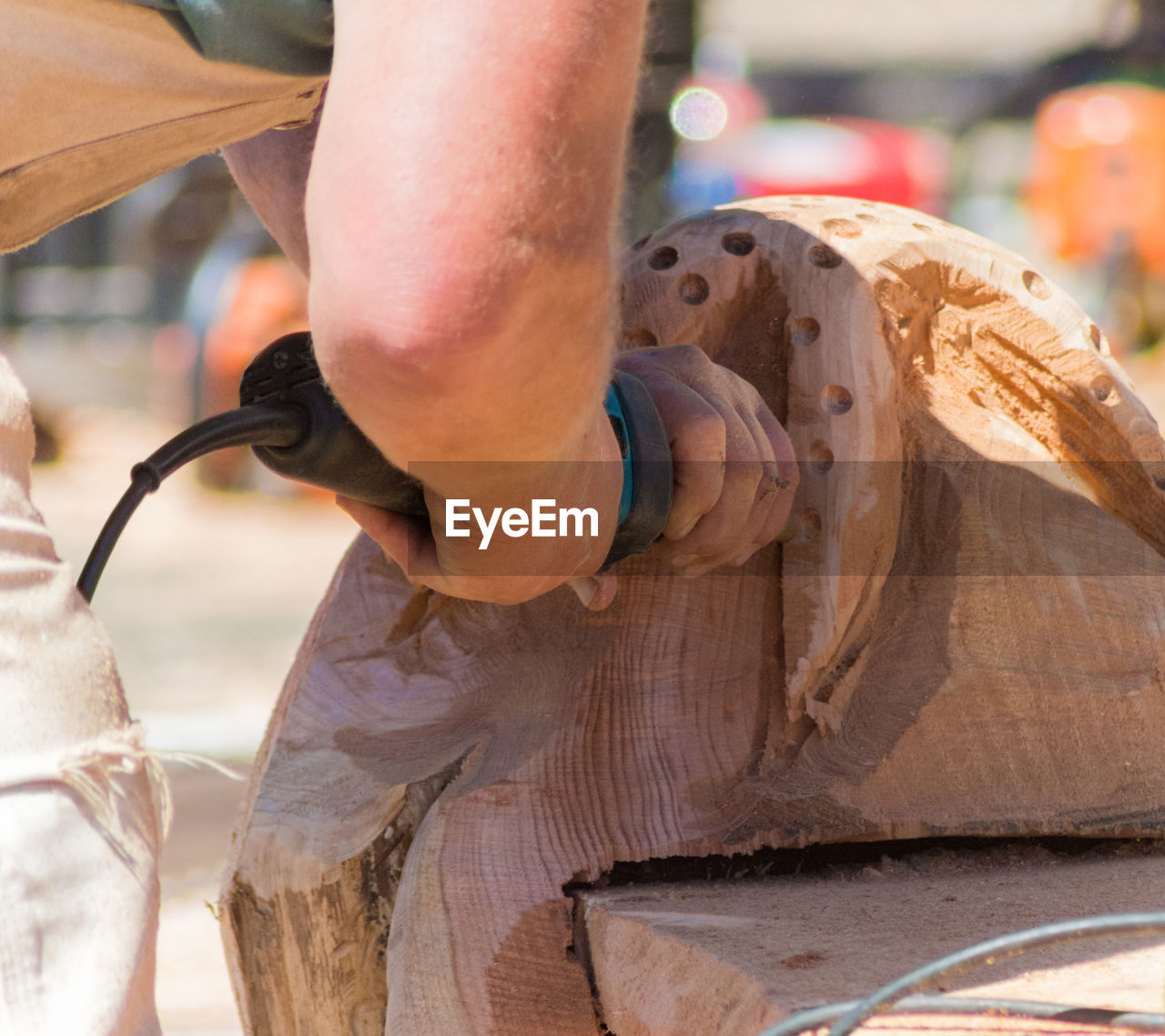 Cropped image of man using drill on wooden sculpture