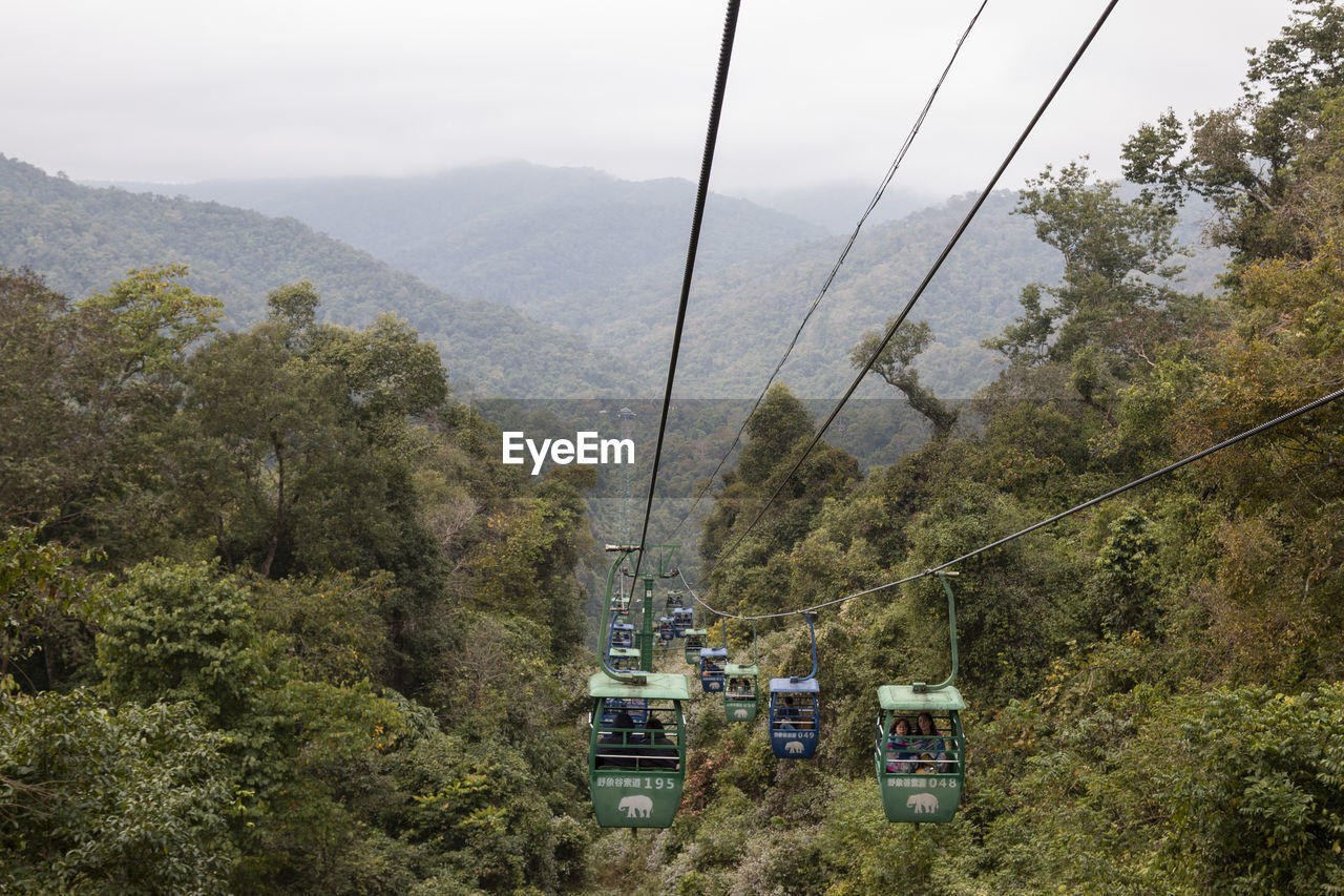 SCENIC VIEW OF OVERHEAD CABLE CAR OVER MOUNTAINS