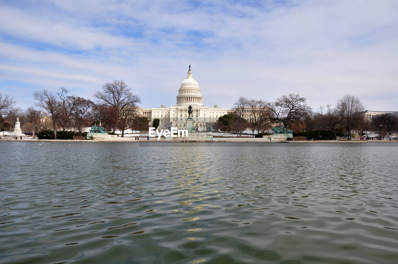 Low Angle View Of Capitol Building In Front Of Lake Against Sky