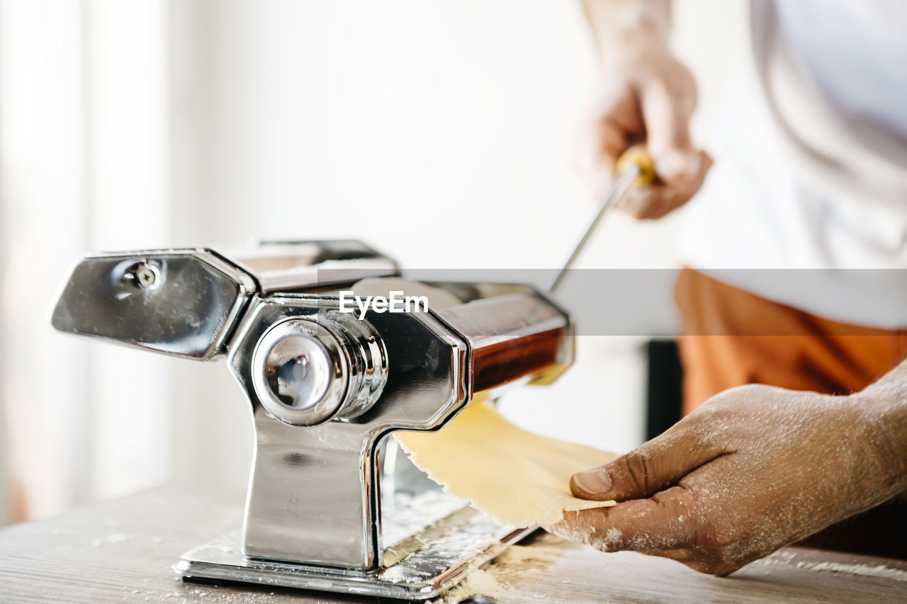 Midsection Of Male Chef Making Food With Machinery On Table