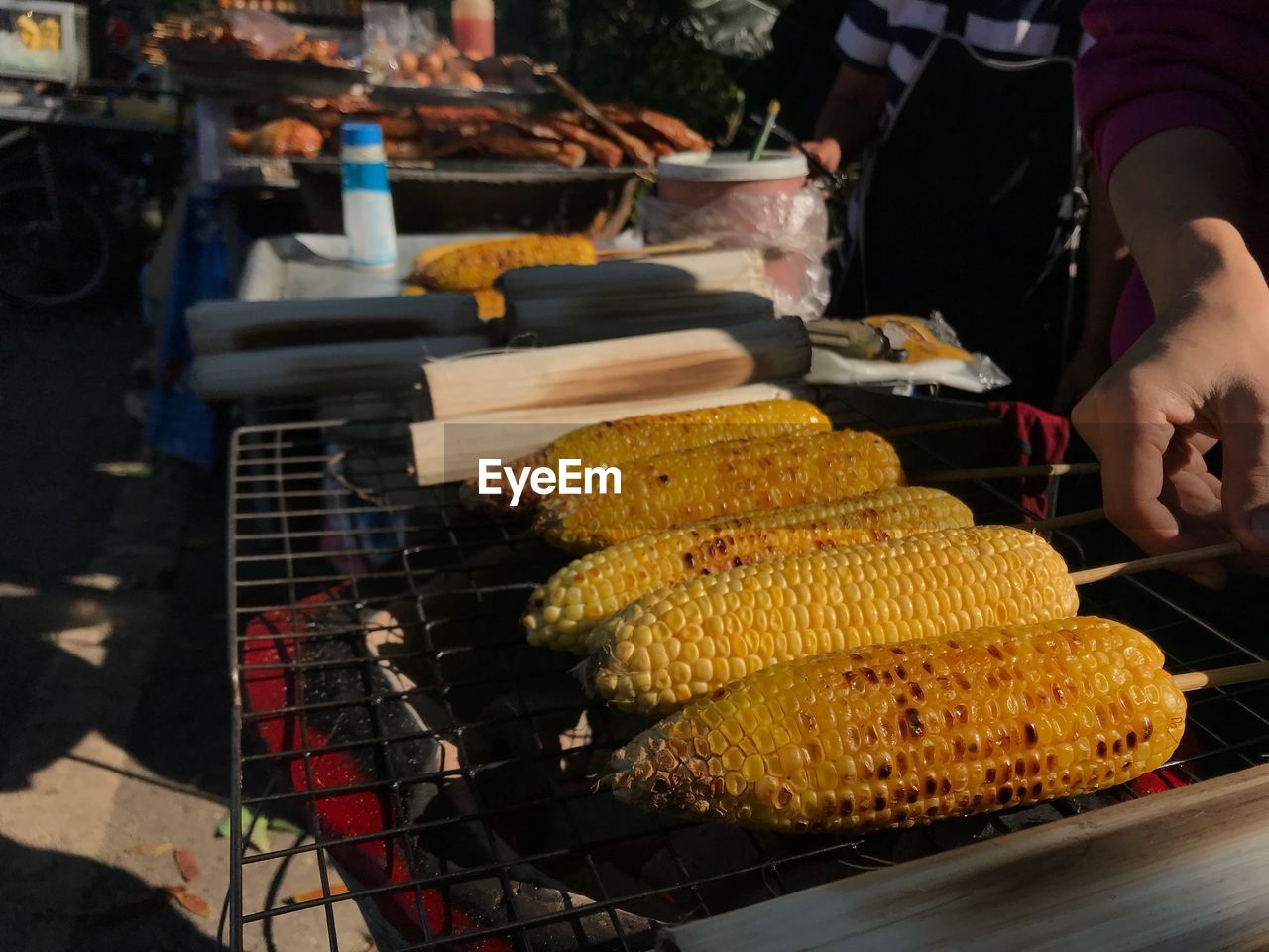 food and drink, food, real people, freshness, for sale, corn on the cob, preparation, corn, barbecue, healthy eating, market, men, retail, night, indoors, one person, occupation, close-up, human hand