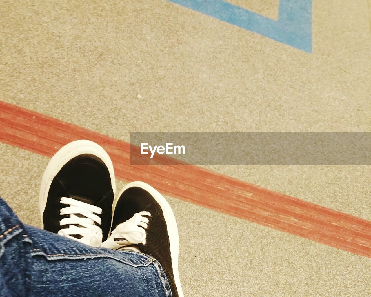 shoe, low section, human leg, real people, personal perspective, human body part, one person, standing, jeans, lifestyles, unrecognizable person, human foot, leisure activity, day, outdoors, high angle view, men, directly above, red, people, adult