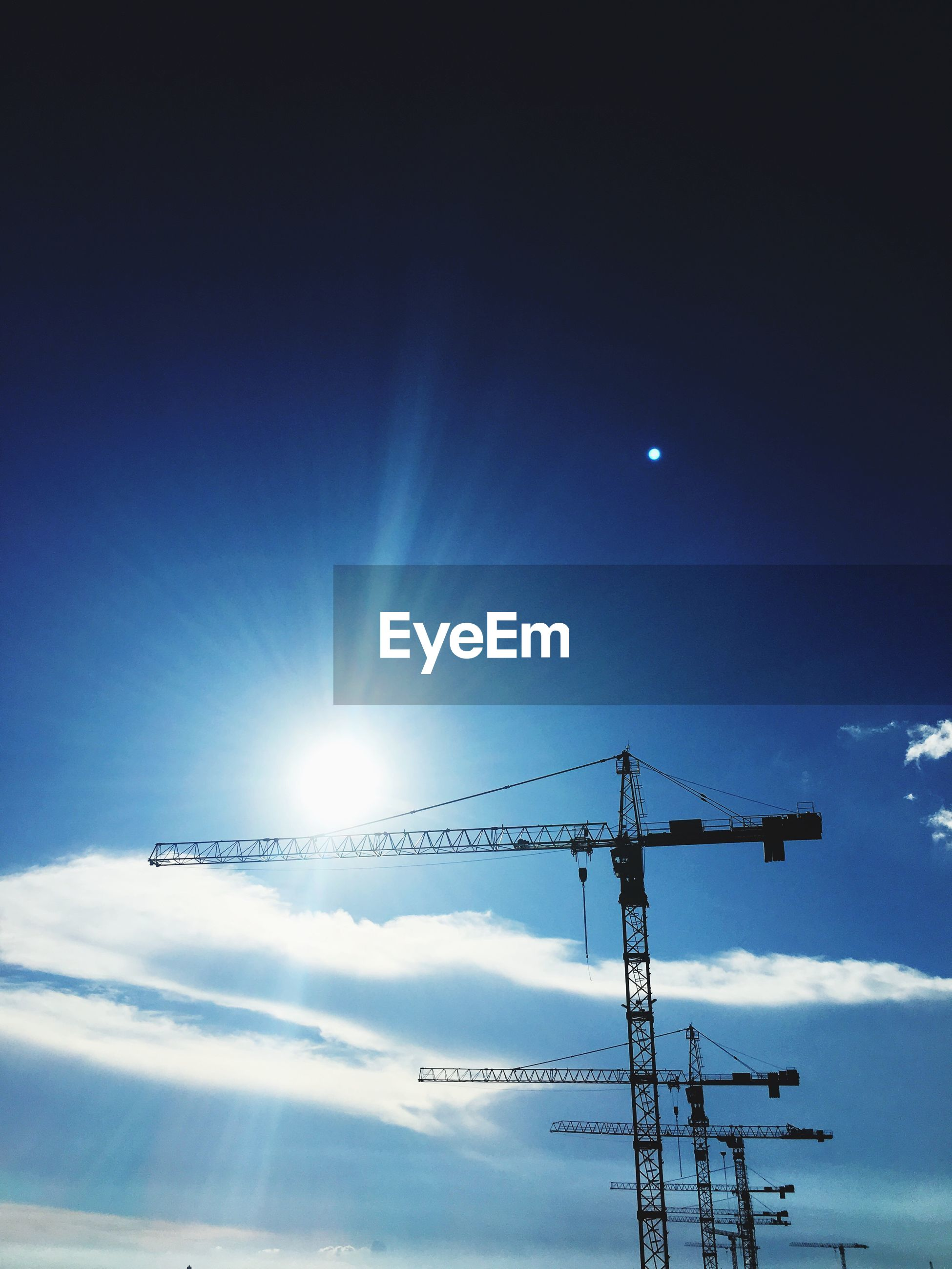 Low angle view of silhouette cranes against blue sky on sunny day