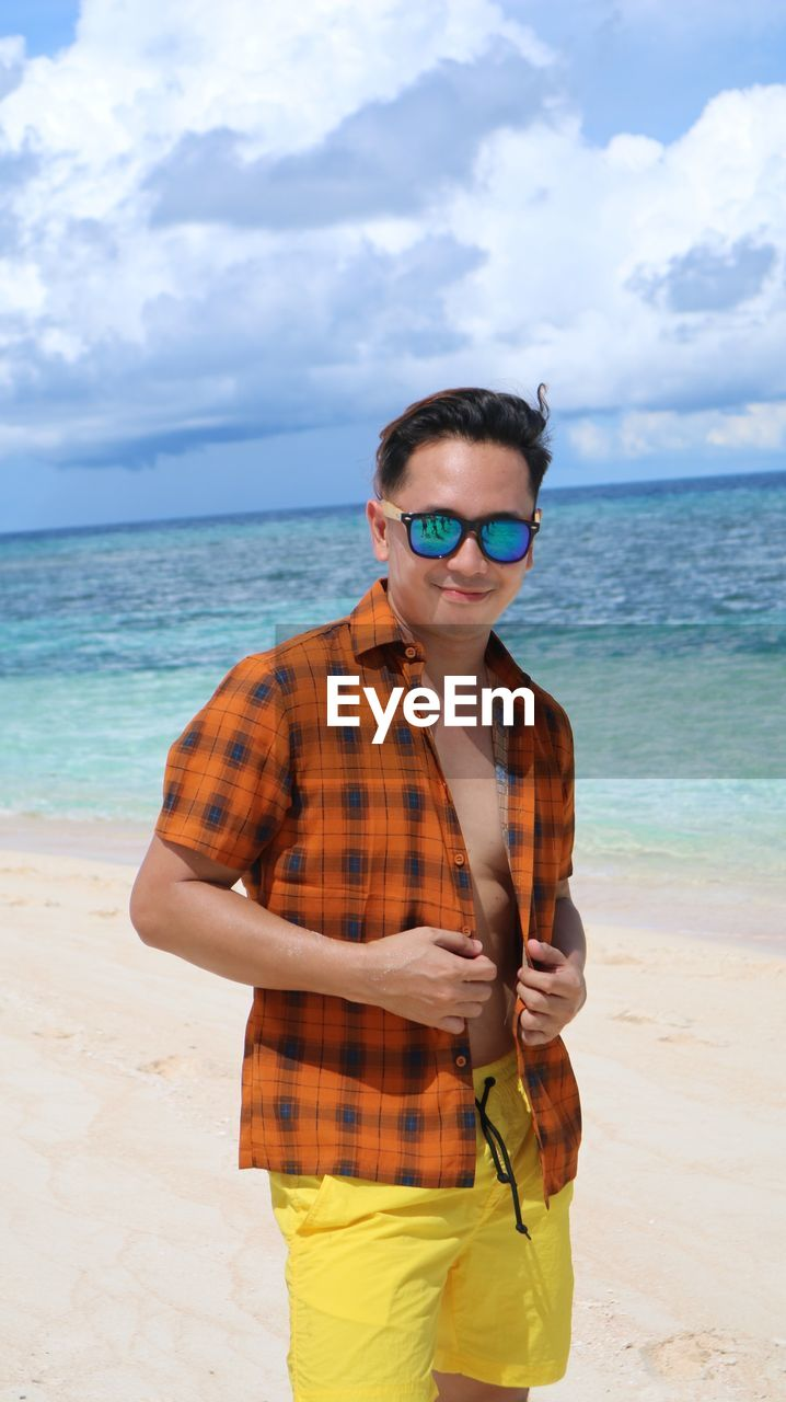Portrait of man in sunglasses standing at beach against sky