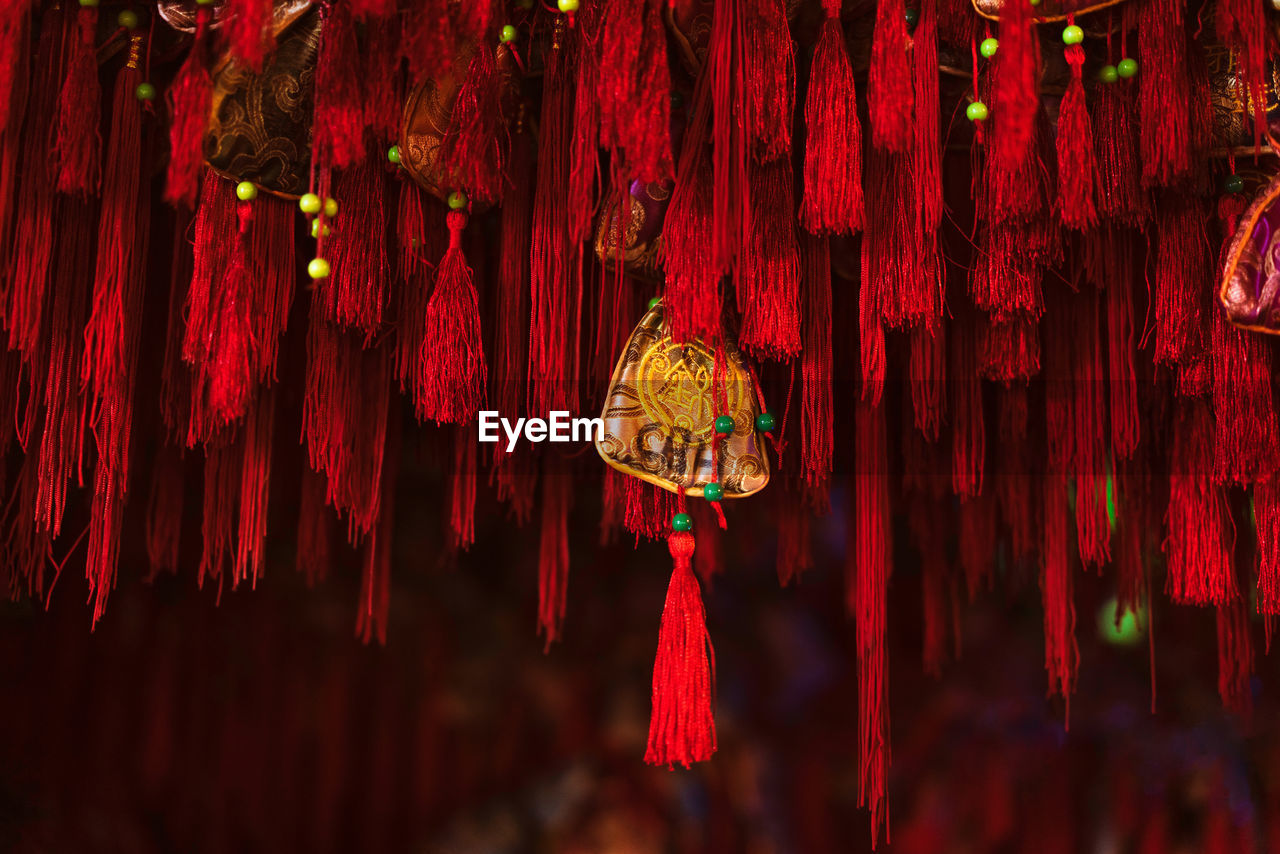 hanging, red, decoration, tassel, no people, textile, close-up, art and craft, market, thread, illuminated, focus on foreground, multi colored, outdoors, for sale, day, selective focus, stage
