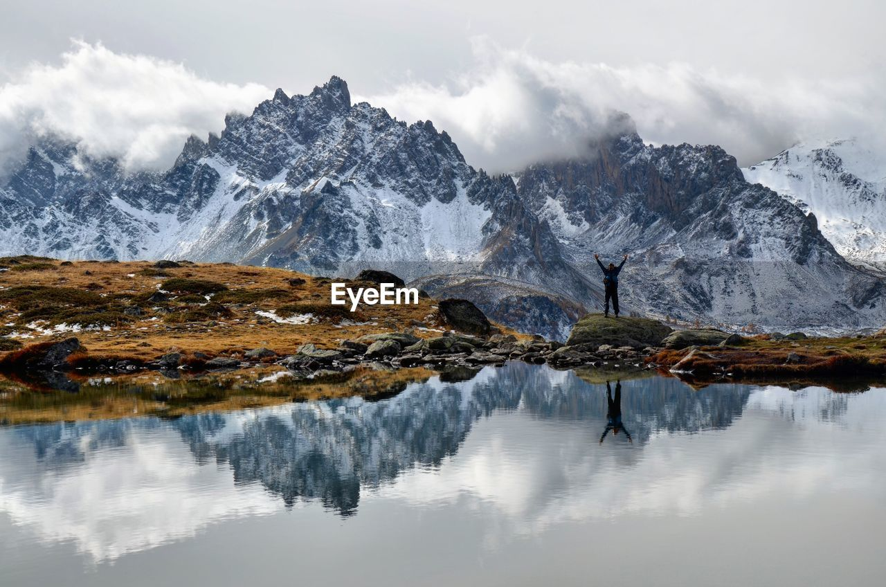 Man with arms raised reflecting on lake by mountains against cloudy sky