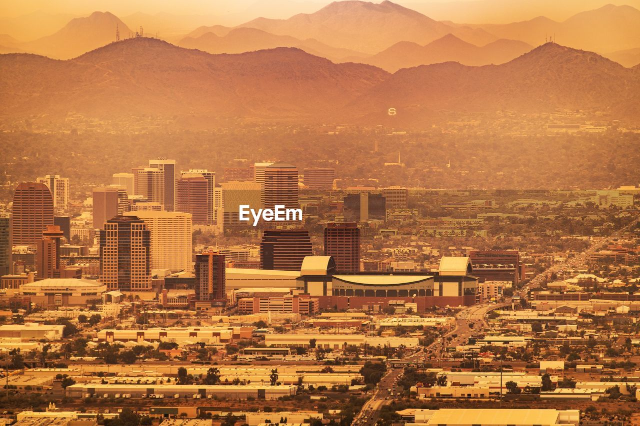 Aerial view of cityscape against mountains during sunset