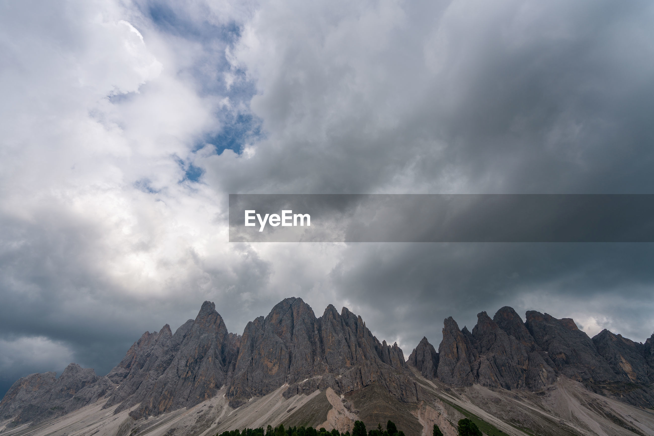 Low angle view of clouds over mountain range against sky