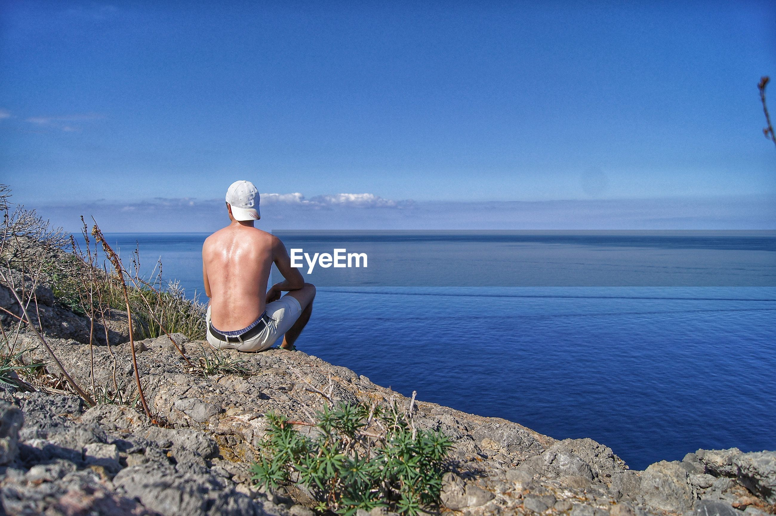 Rear view of shirtless man sitting by sea on rock