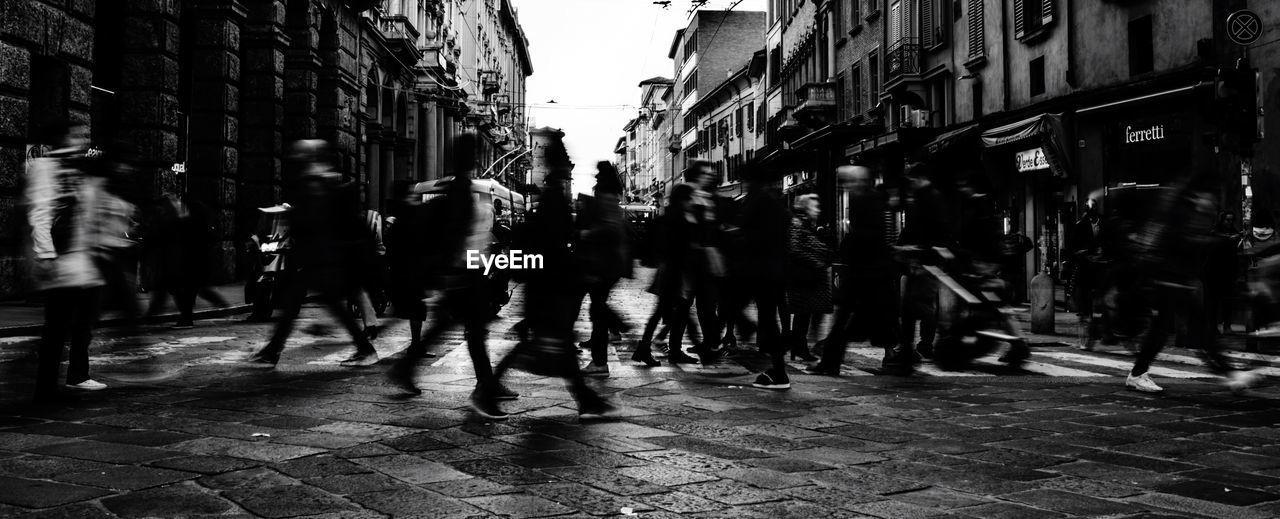Silhouette people walking on street in city