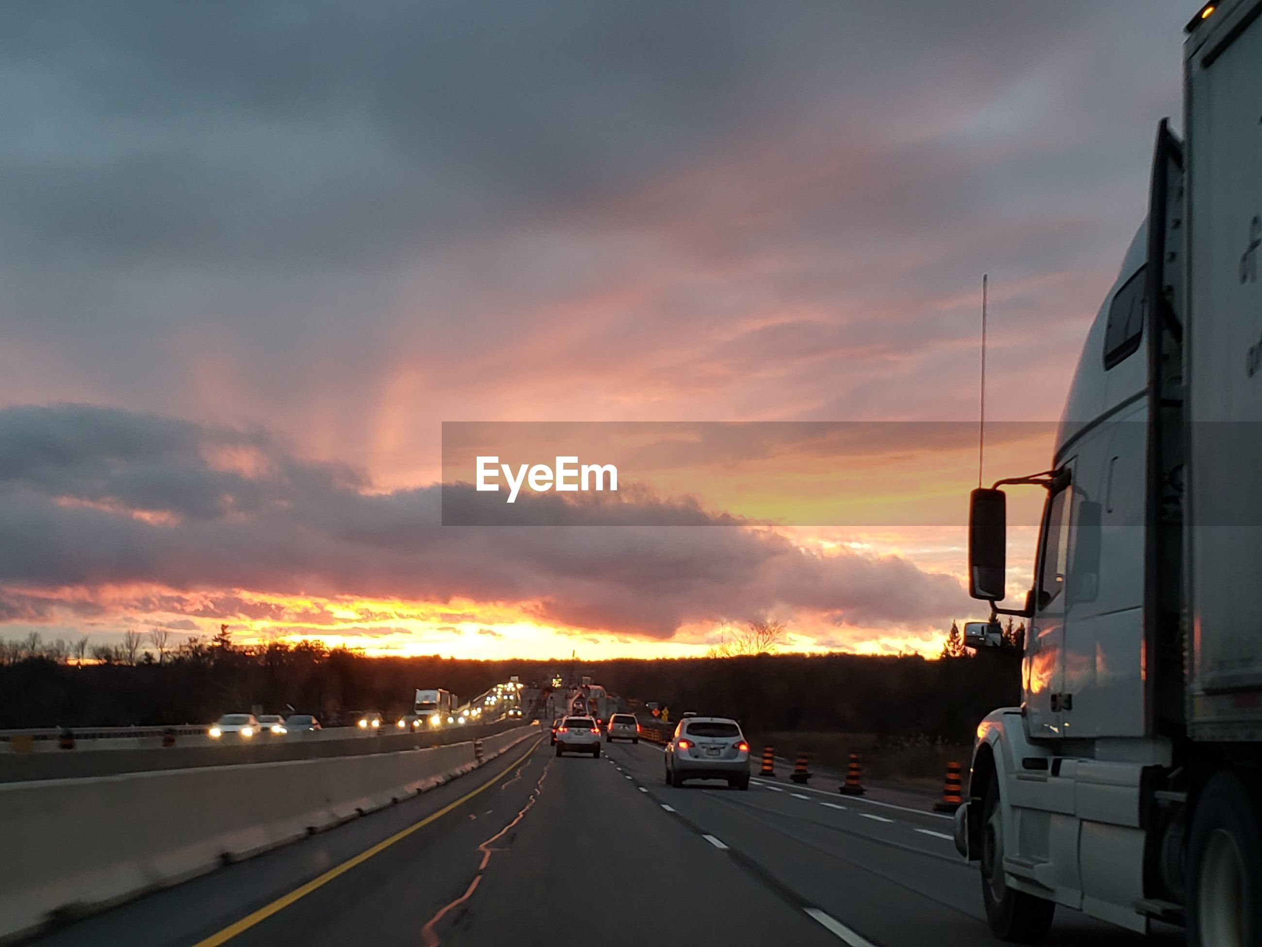 Cars on road against dramatic sky during sunset