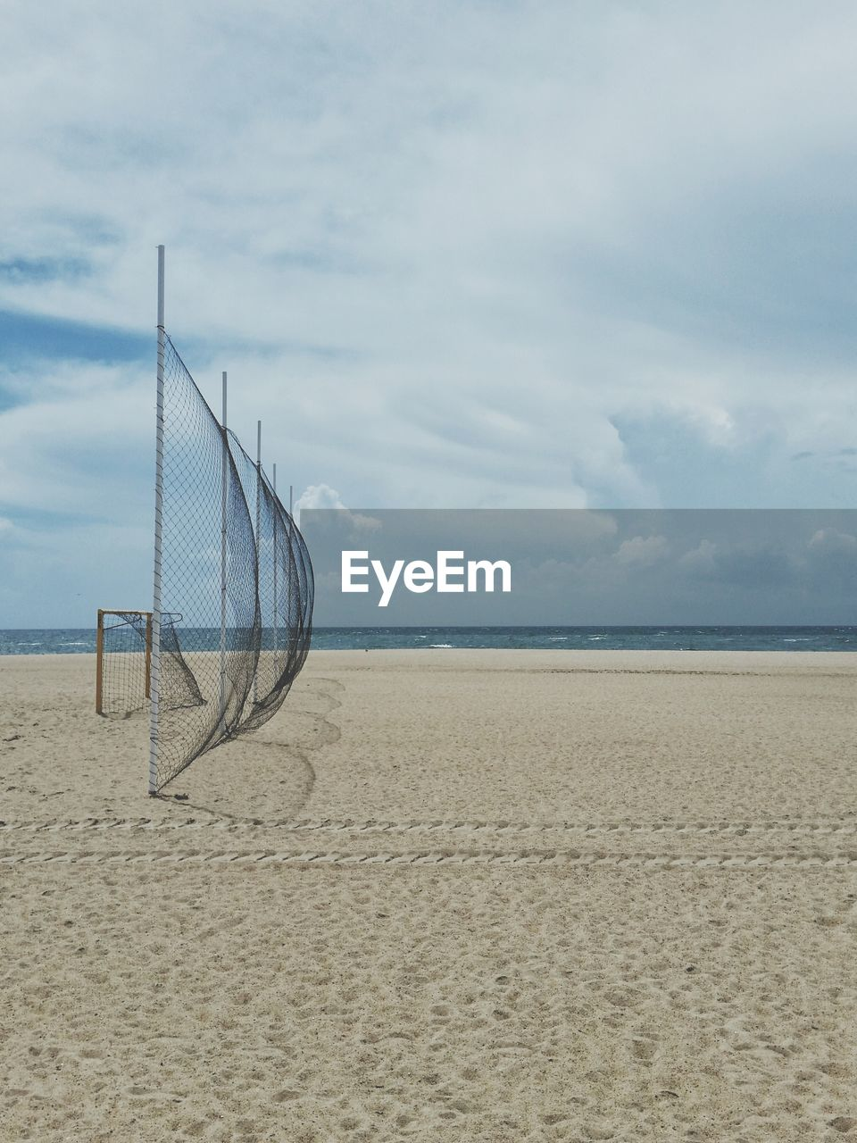 beach, sky, land, cloud - sky, sand, sea, water, scenics - nature, net - sports equipment, beauty in nature, nature, day, horizon over water, horizon, tranquility, volleyball - sport, tranquil scene, outdoors, beach volleyball, no people