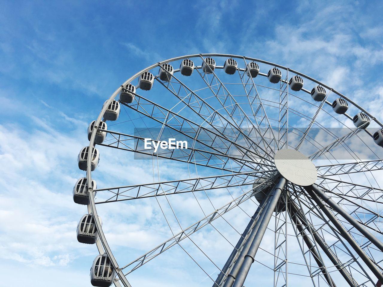 sky, ferris wheel, amusement park, arts culture and entertainment, low angle view, amusement park ride, cloud - sky, nature, geometric shape, circle, no people, blue, shape, day, fairground, outdoors, built structure, large, architecture, metal, spoke
