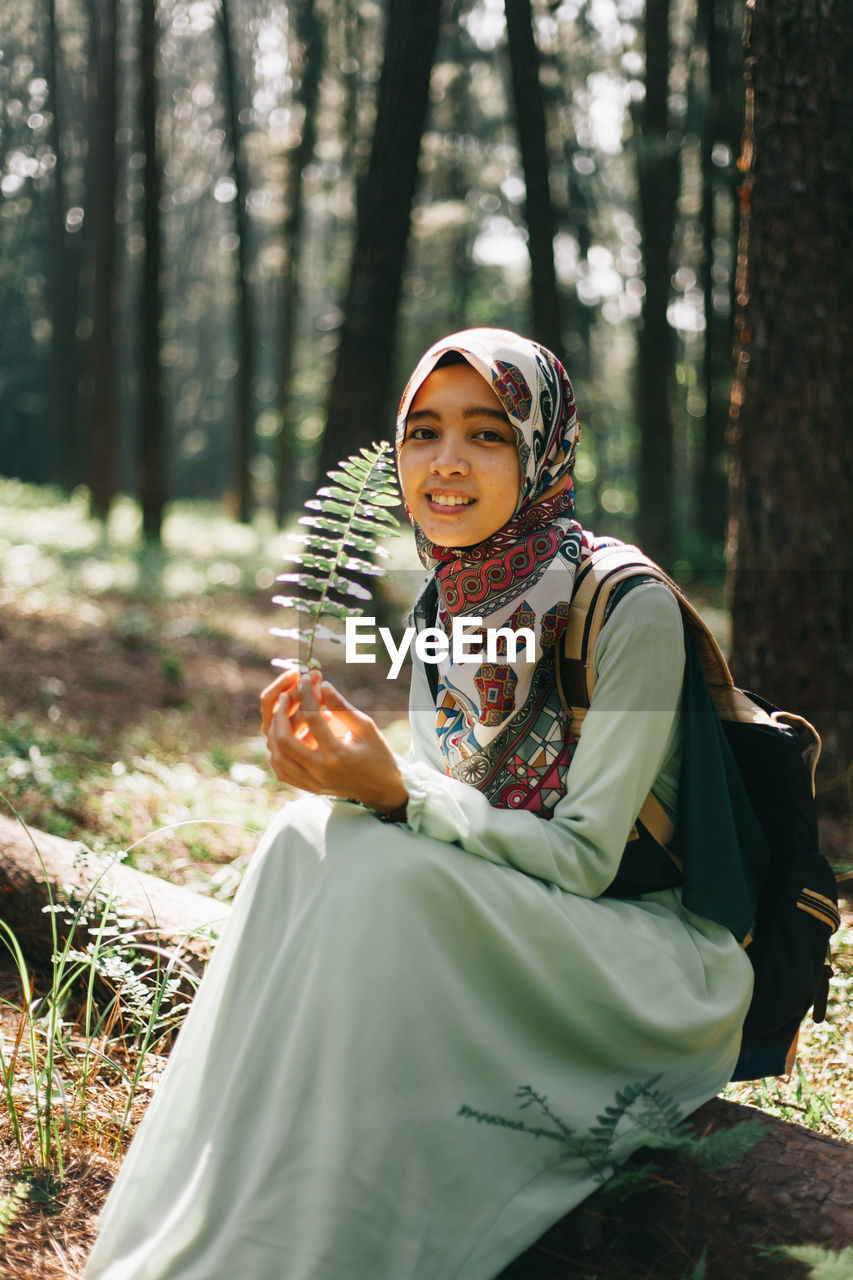 PORTRAIT OF SMILING WOMAN SITTING IN FOREST