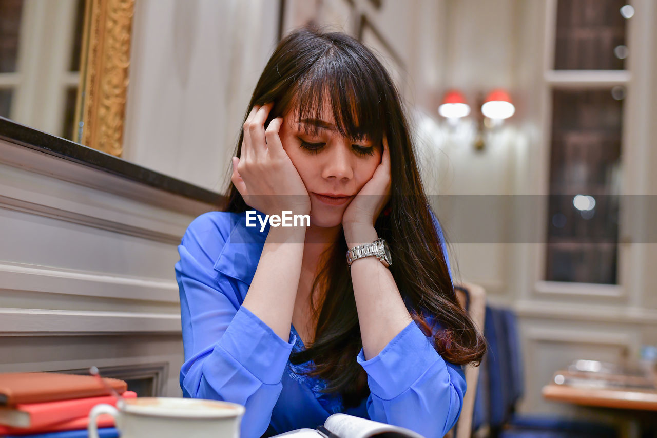 one person, sitting, real people, indoors, hand, front view, women, table, lifestyles, females, girls, child, head in hands, emotion, focus on foreground, hairstyle, portrait, waist up, sadness, innocence, bangs, teenager