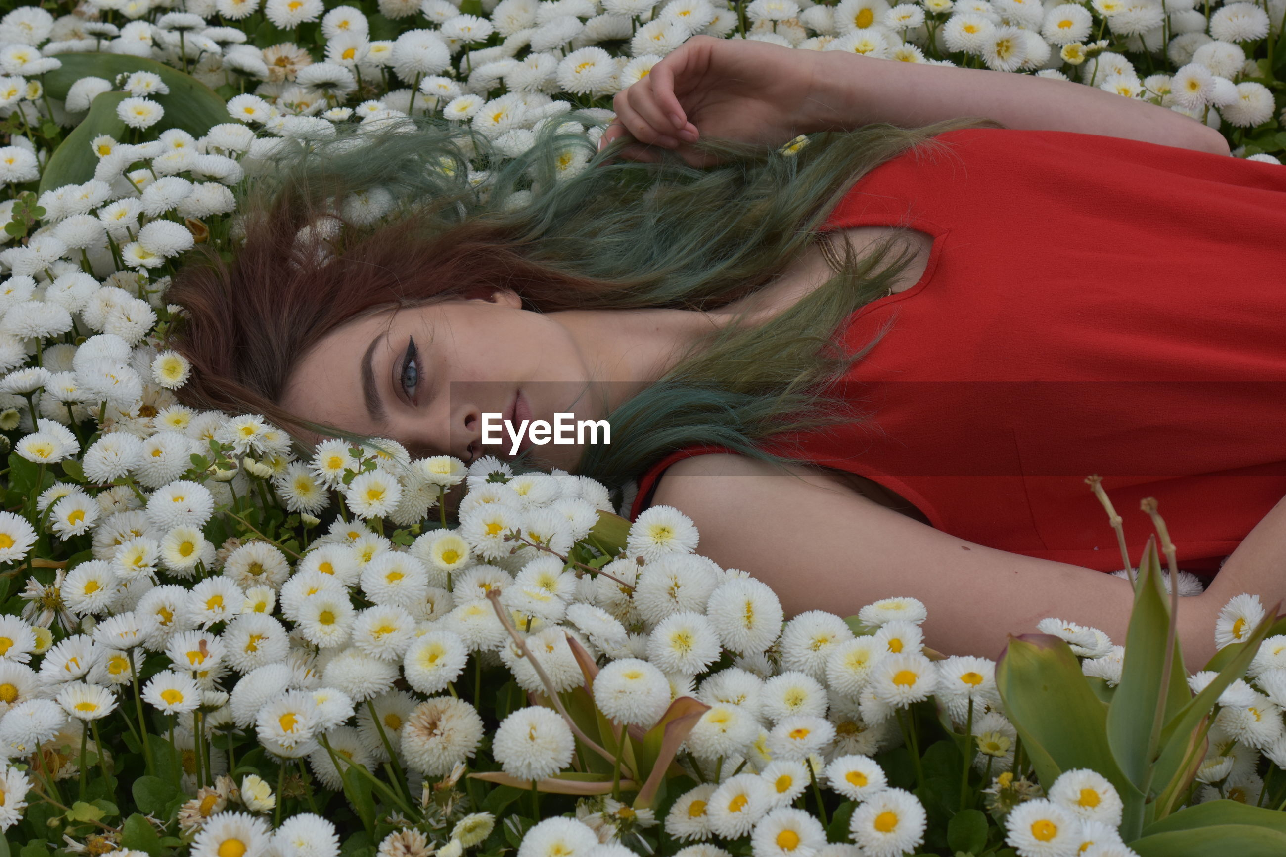 Portrait of young woman lying on flowers
