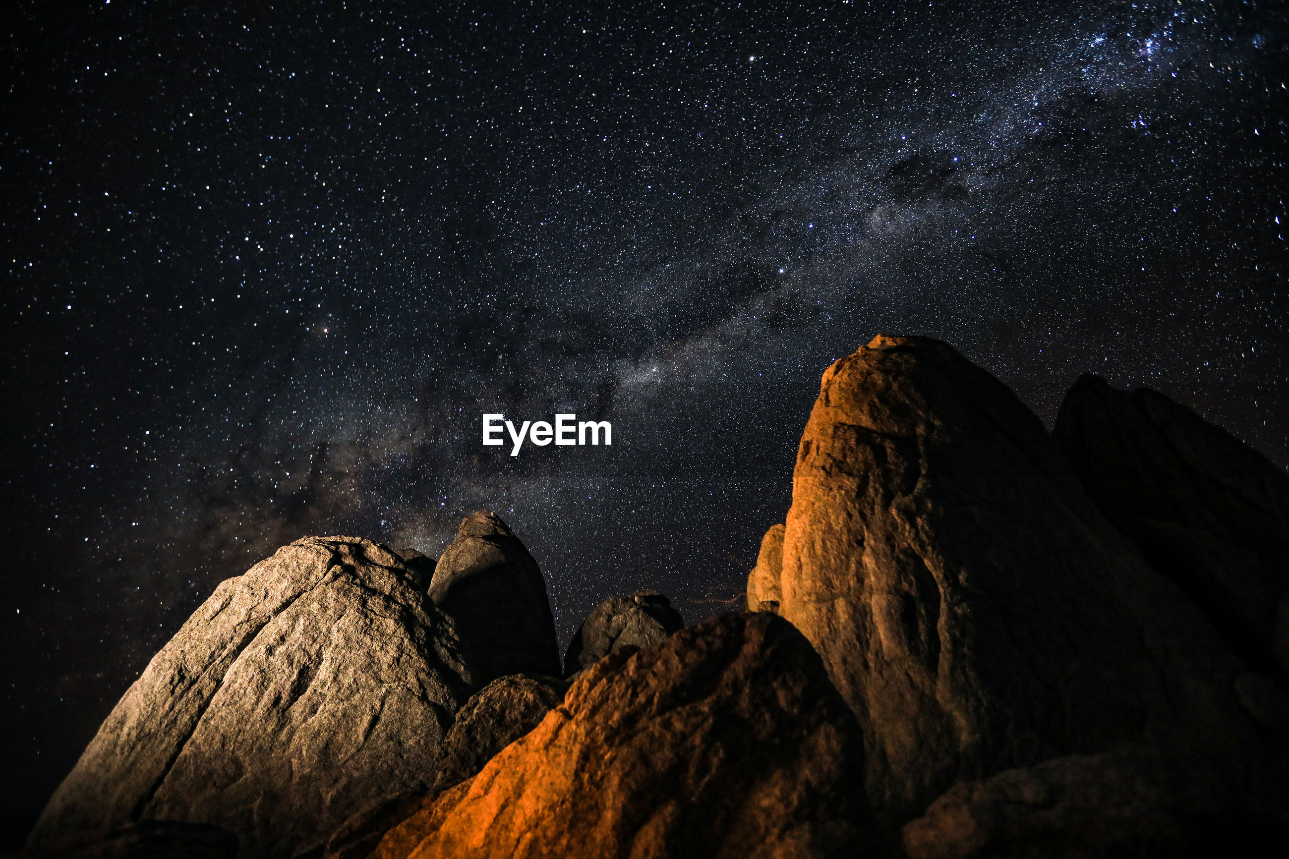 Low angle view of rock formations against star field at night