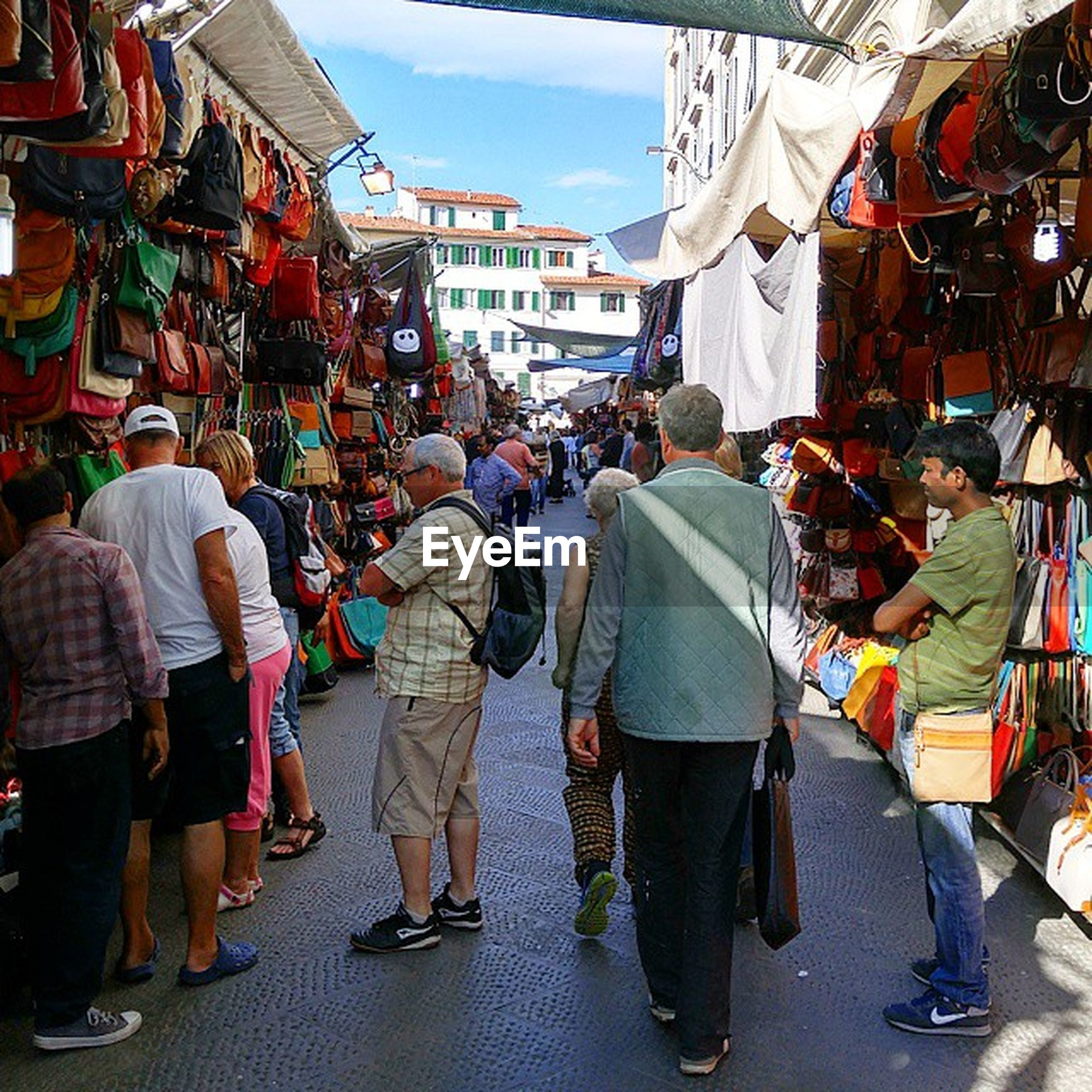 men, large group of people, market, person, street, building exterior, walking, market stall, built structure, architecture, lifestyles, city, retail, city life, shopping, street market, crowd, store, rear view