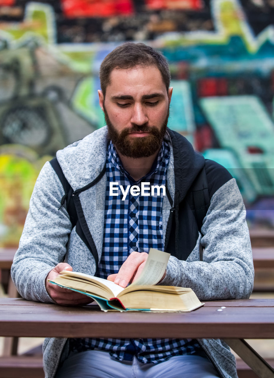 one person, beard, sitting, front view, facial hair, book, publication, real people, table, focus on foreground, casual clothing, young adult, young men, activity, portrait, holding, lifestyles, leisure activity, studying