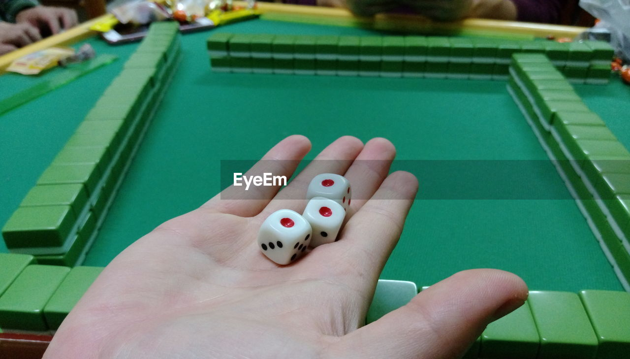 Cropped Image Of Hand Holding Dices While Playing Mahjong