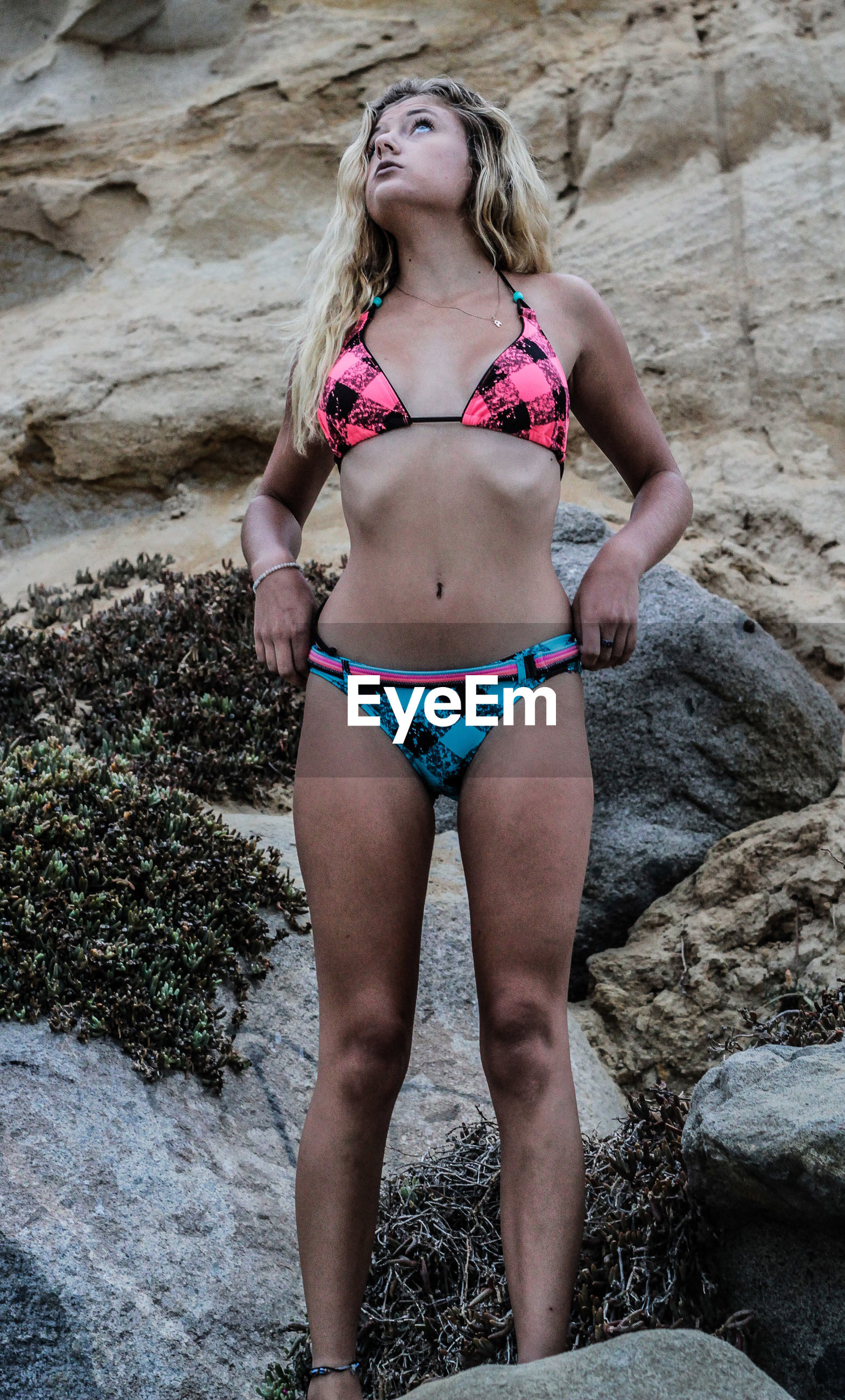 Young woman looking up while wearing bikini on rock