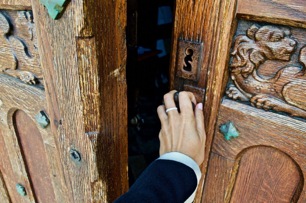Cropped Hand Of Woman Opening Wooden Door