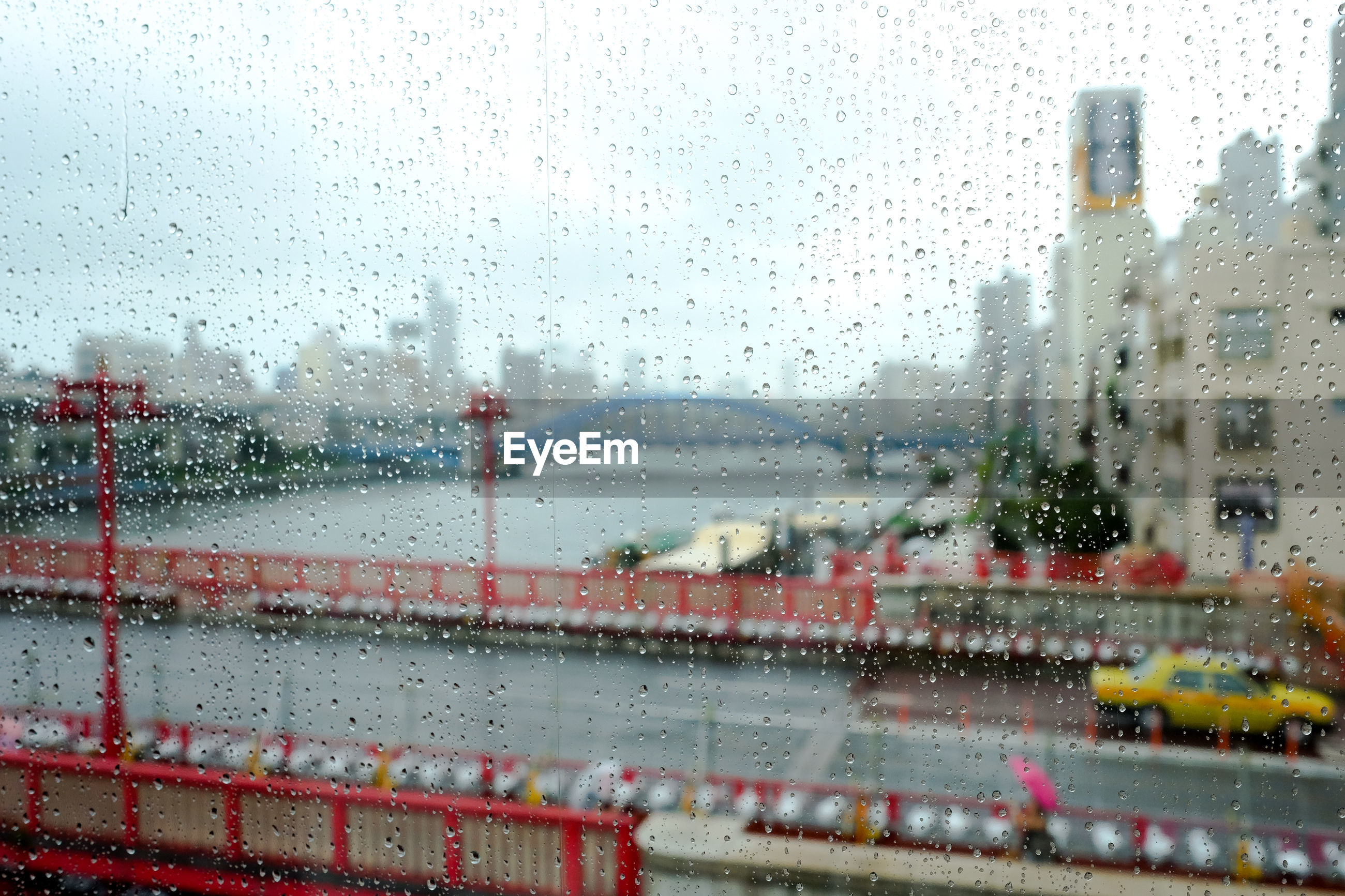 Bridge over river against sky seen from wet glass at asakusa