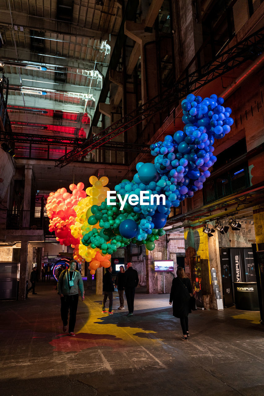 architecture, built structure, city, building exterior, group of people, real people, incidental people, multi colored, men, night, illuminated, store, people, decoration, street, retail, lifestyles, women, city life, adult