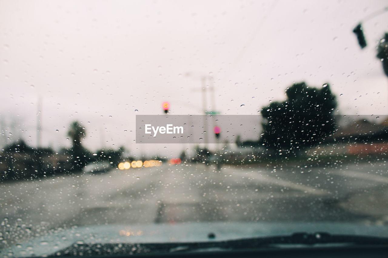 Road Against Sky Seen Through Wet Car Windshield During Rainy Season