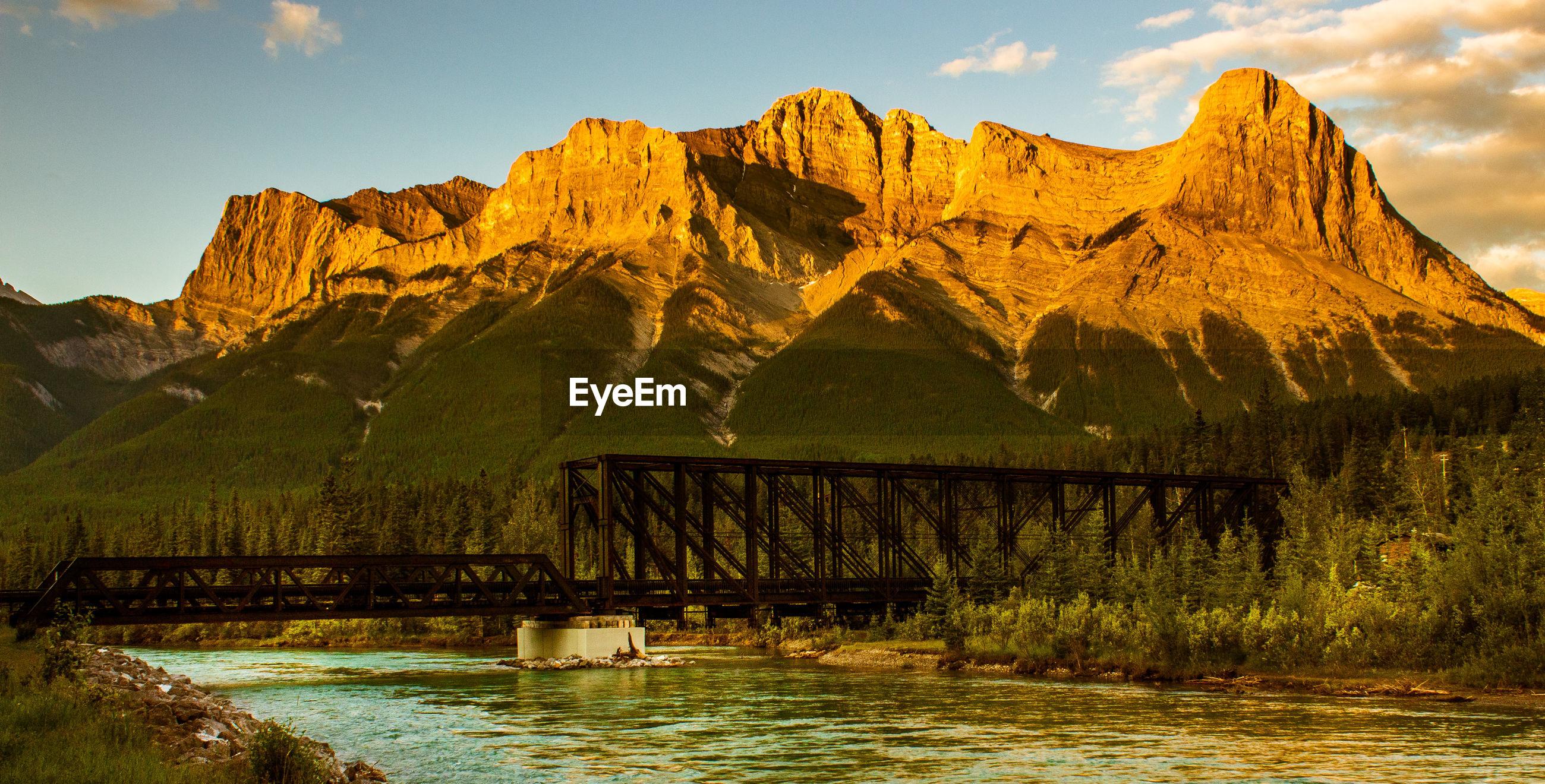 Bridge over river against mountain range