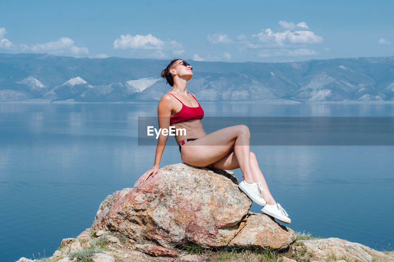 YOUNG WOMAN STANDING ON ROCK AGAINST MOUNTAIN