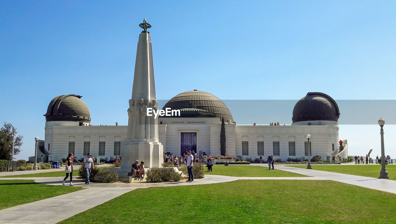 architecture, dome, built structure, travel destinations, clear sky, tourism, large group of people, travel, grass, building exterior, activity, blue, day, real people, outdoors, sky, people