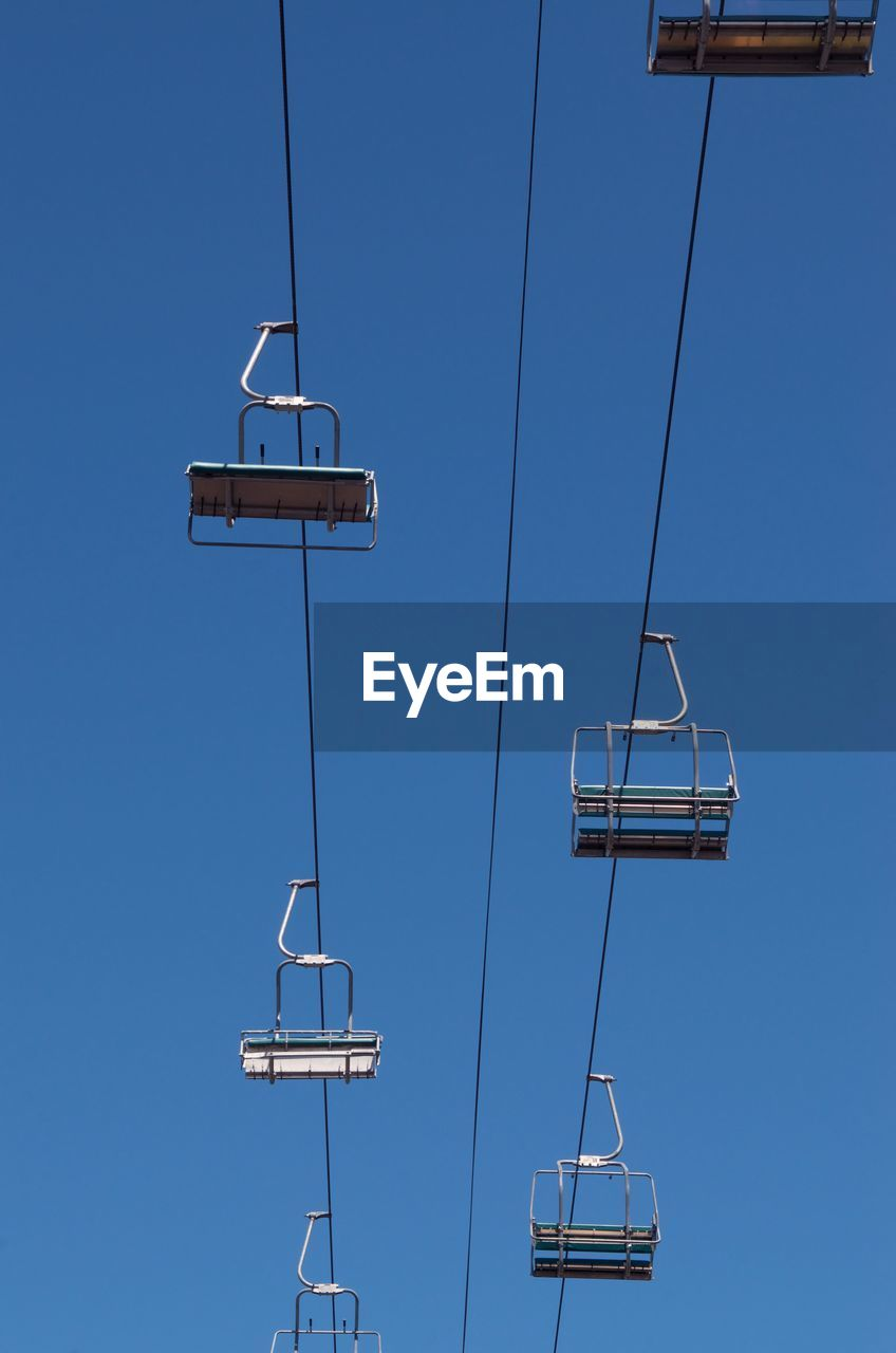 sky, blue, clear sky, ski lift, low angle view, cable car, day, nature, no people, overhead cable car, transportation, cable, outdoors, connection, mode of transportation, communication, sunlight, electricity, travel, technology, power supply