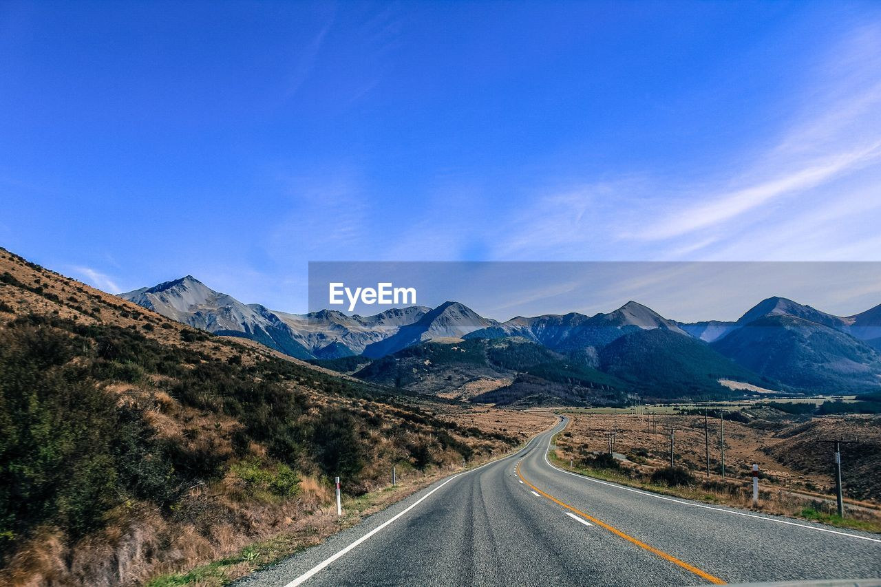Empty Road Leading Towards Mountains Against Blue Sky