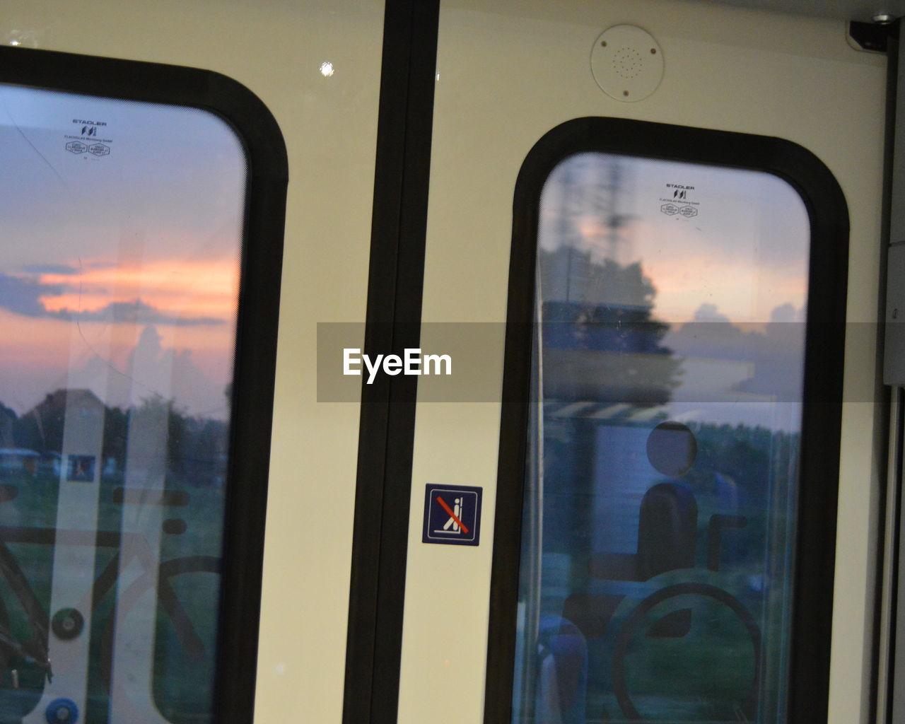 VIEW OF SUNSET SEEN THROUGH TRAIN WINDOW