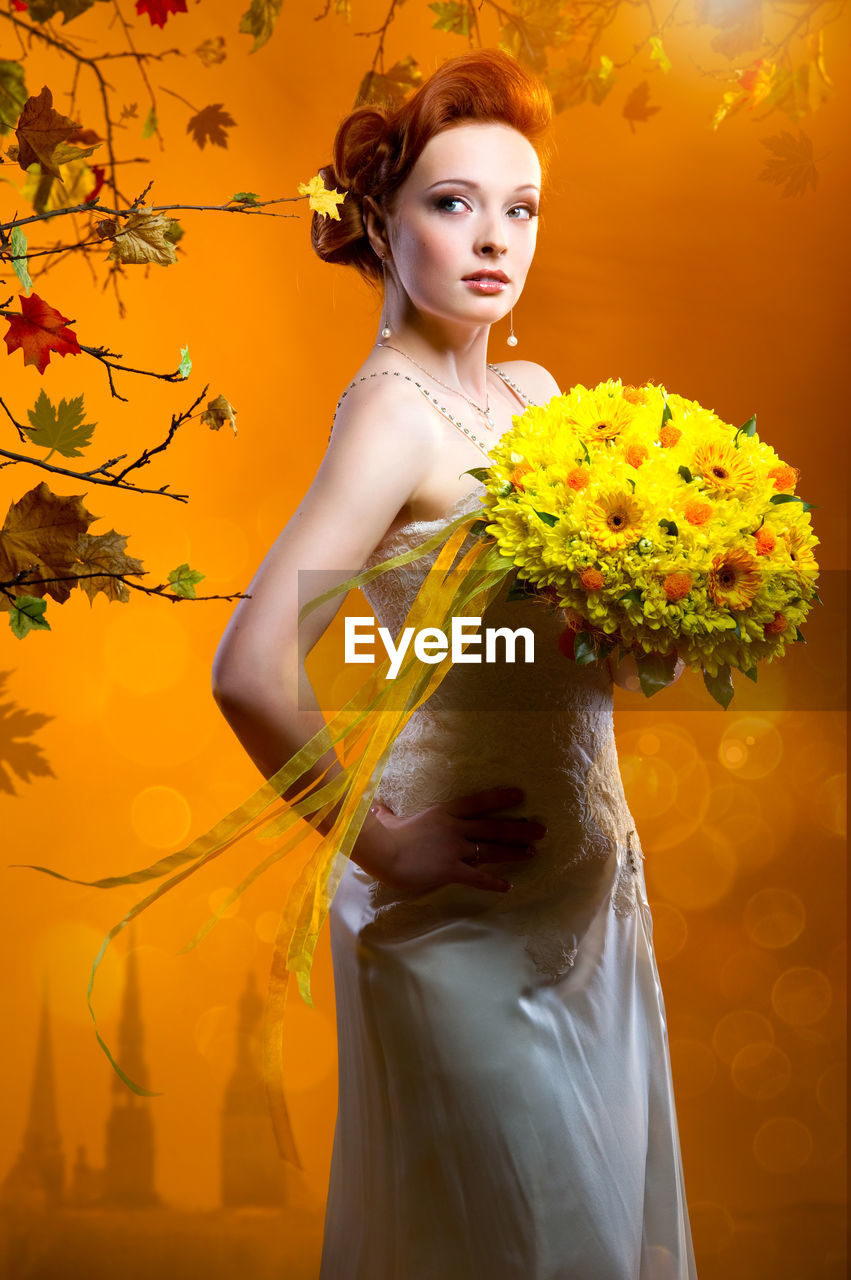 Beautiful Bride Holding Bouquet While Standing Against Orange Background