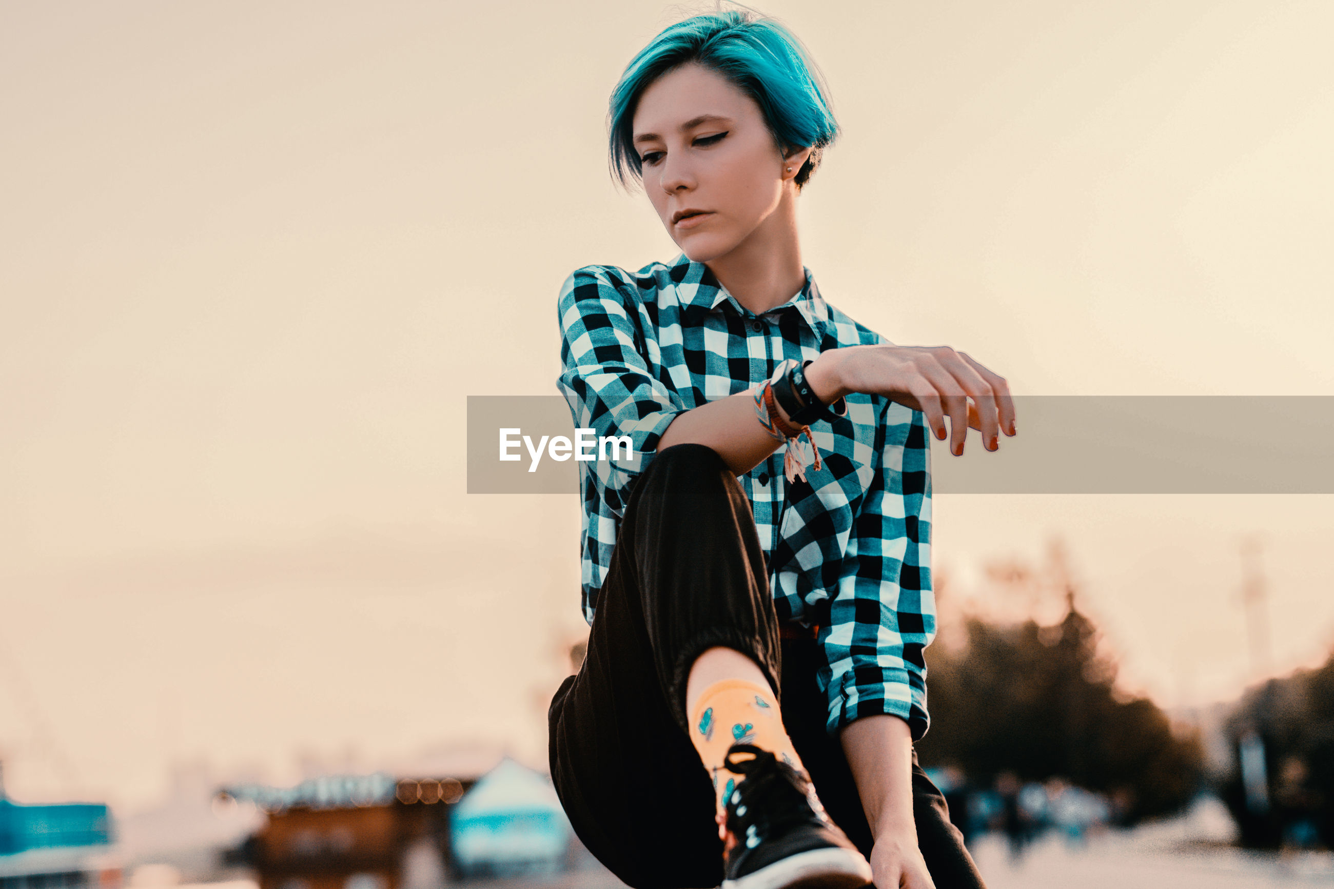 Beautiful woman looking away against sky during sunset