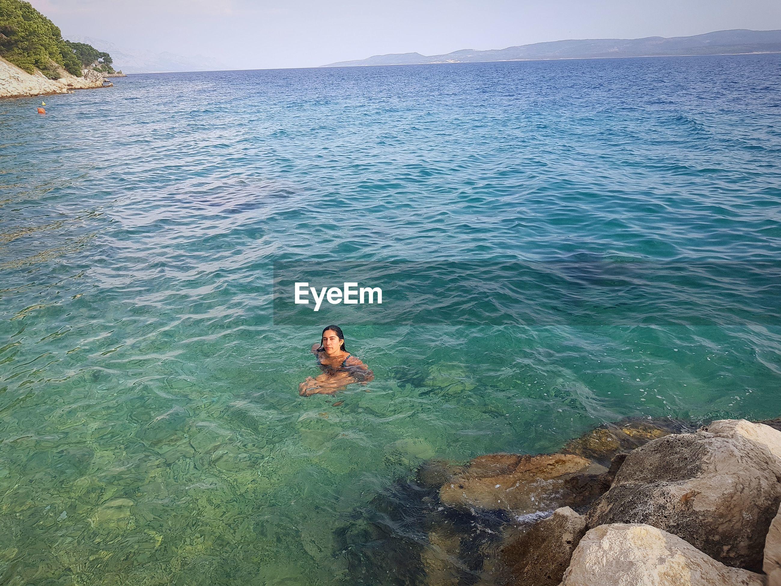 Man on rock in sea