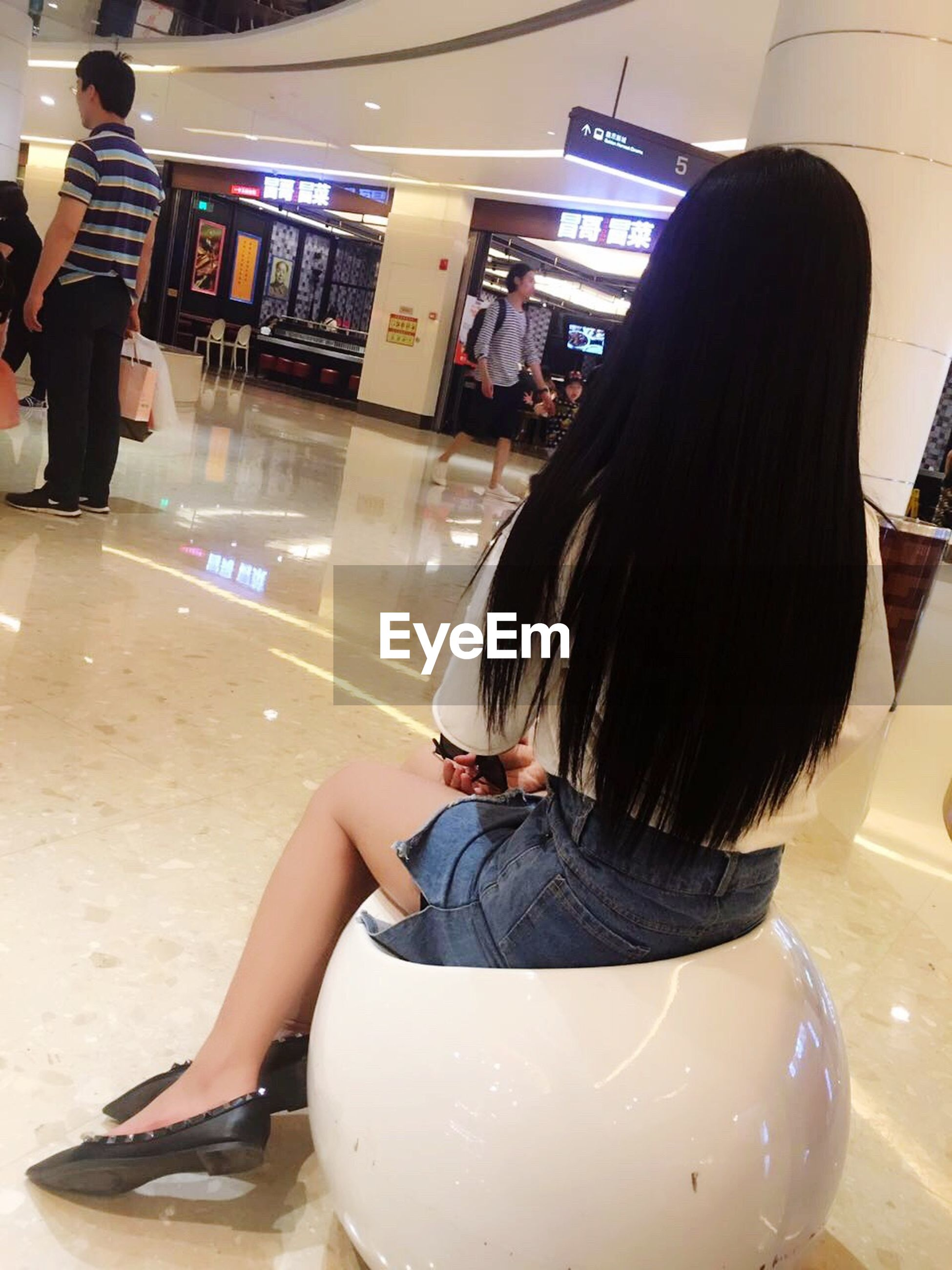 lifestyles, indoors, casual clothing, leisure activity, person, rear view, long hair, standing, young women, side view, young adult, sitting, full length, holding, childhood, incidental people, glass - material