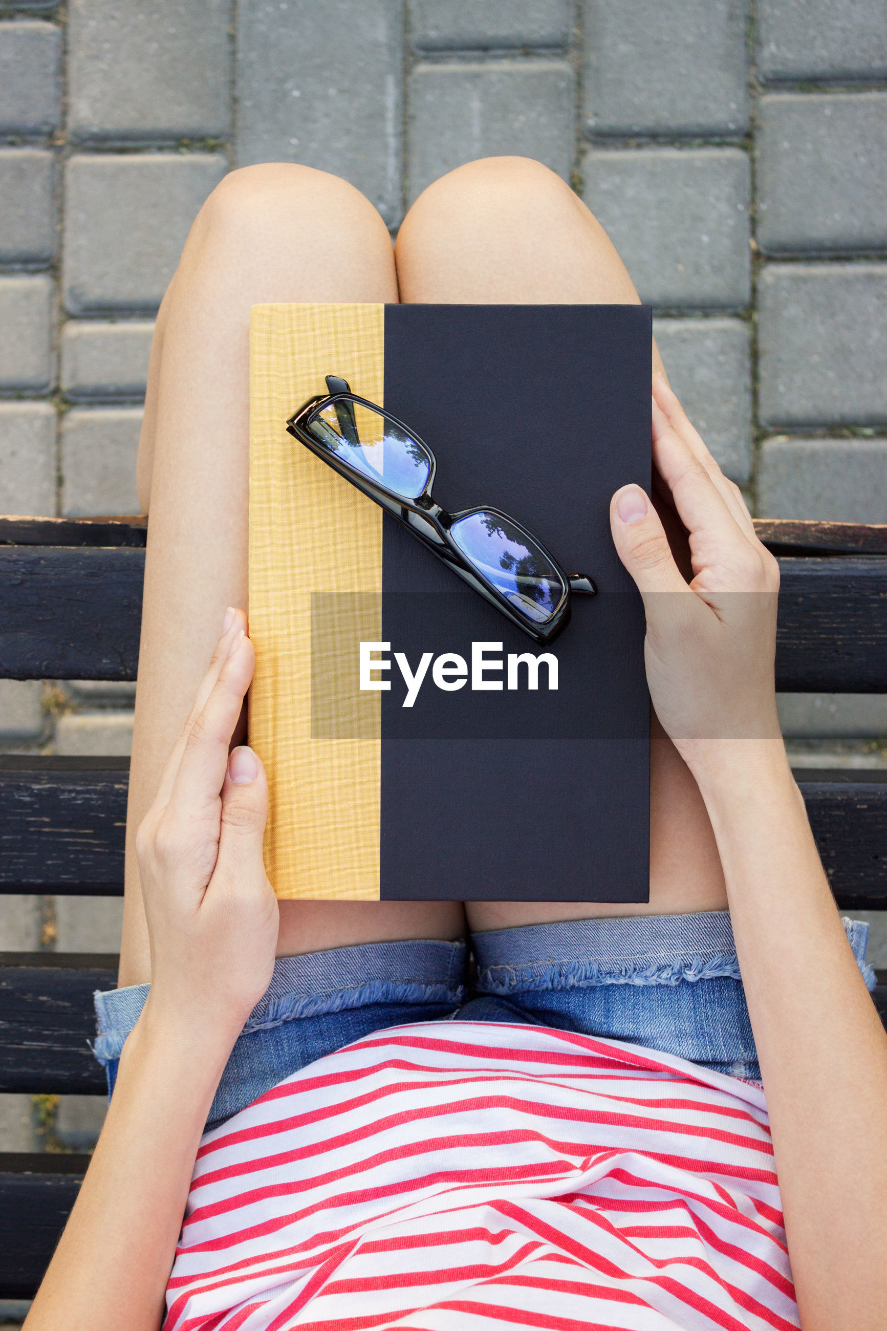Midsection of woman sitting with eyeglasses and diary on bench