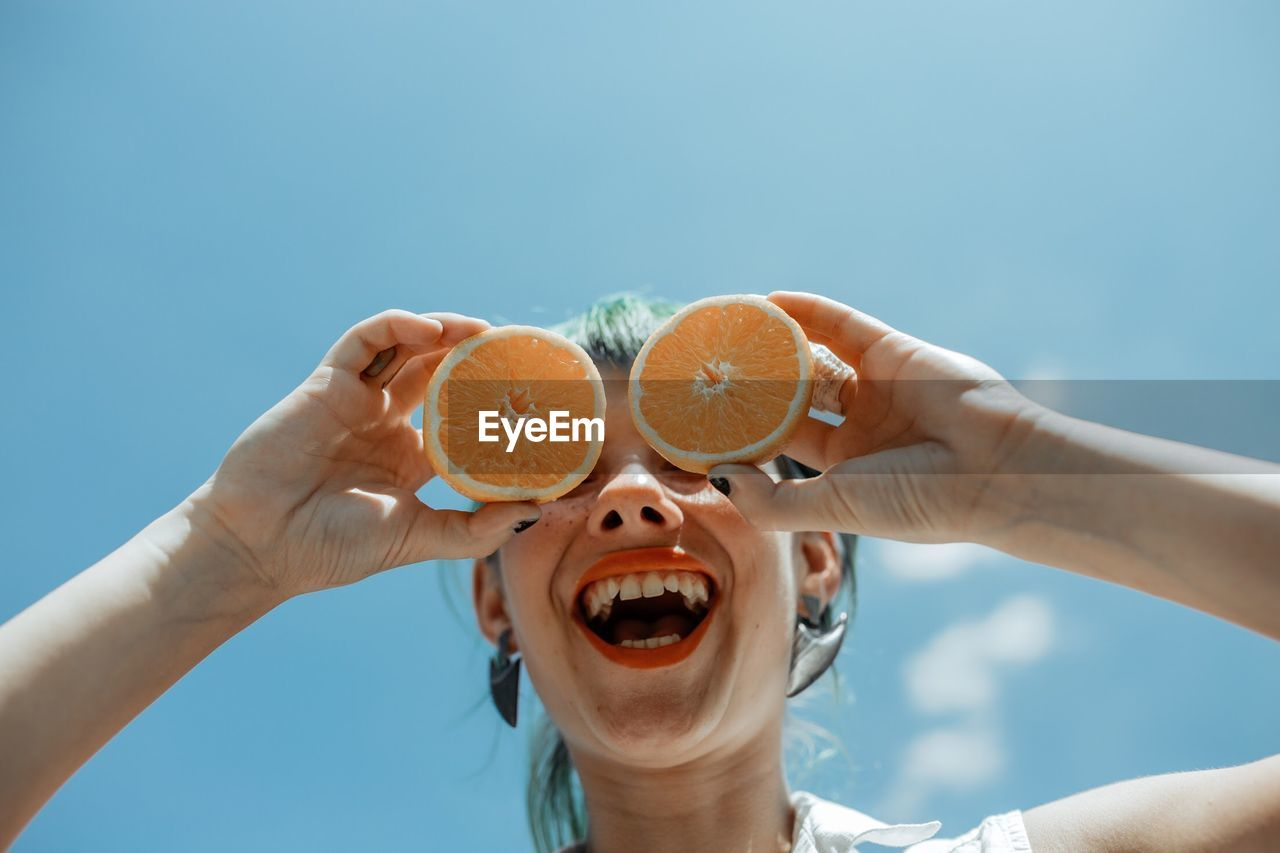 Low Angle View Of Cheerful Woman Holding Orange Slices Against Blue Sky