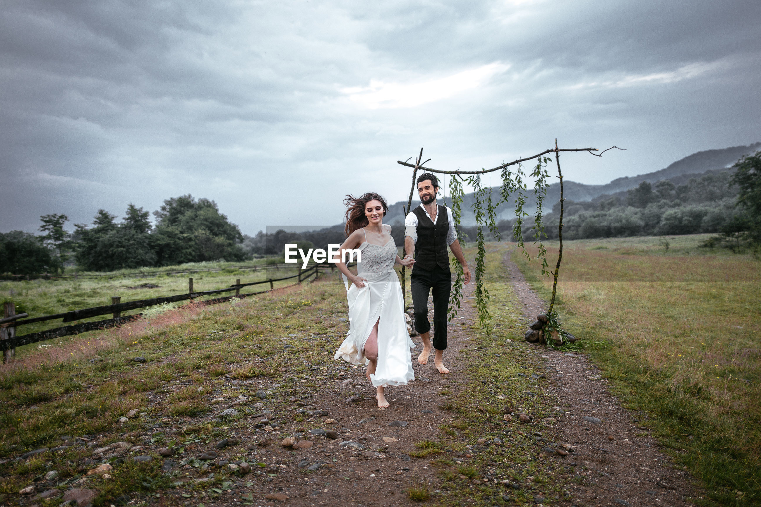 Beautiful woman holding hands of man while running on grassy field