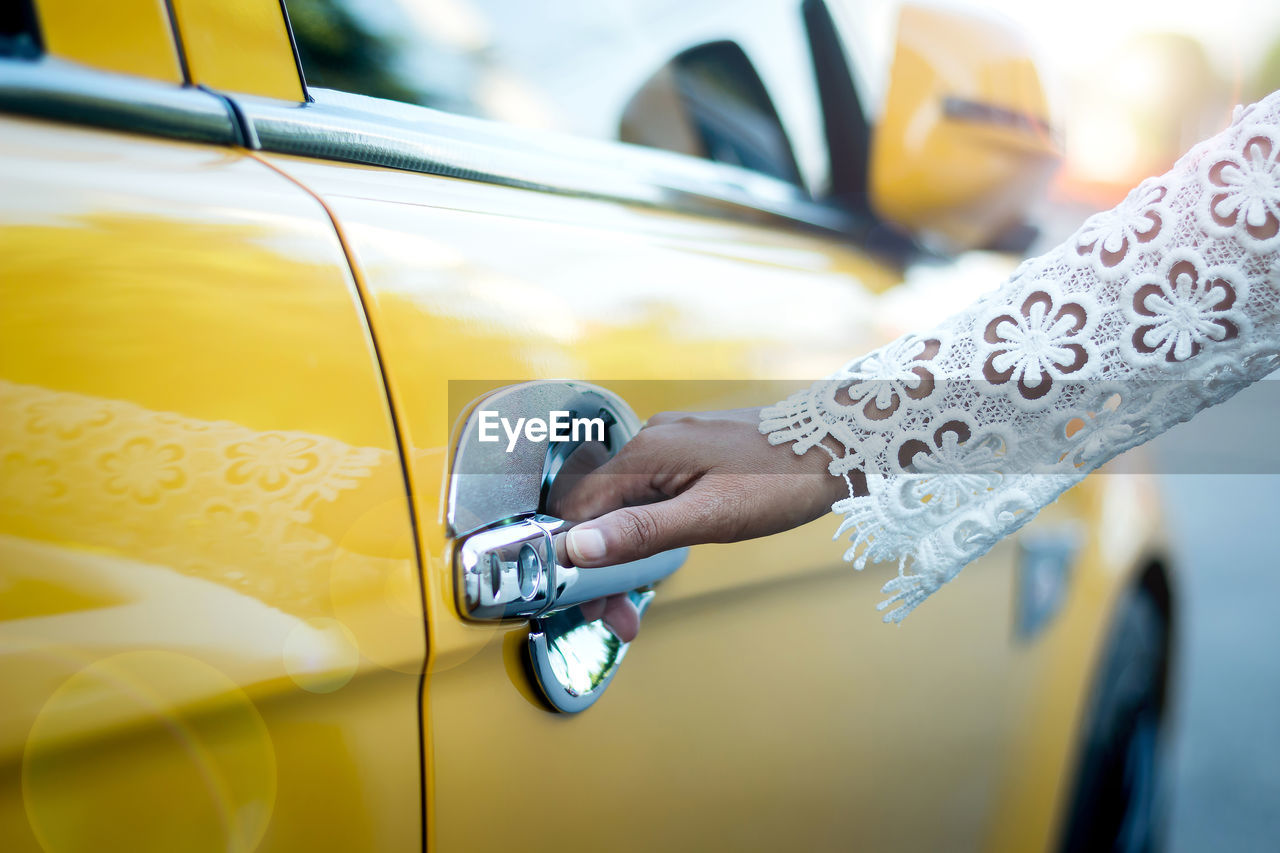 Cropped Hand Of Woman Opening Yellow Car Door