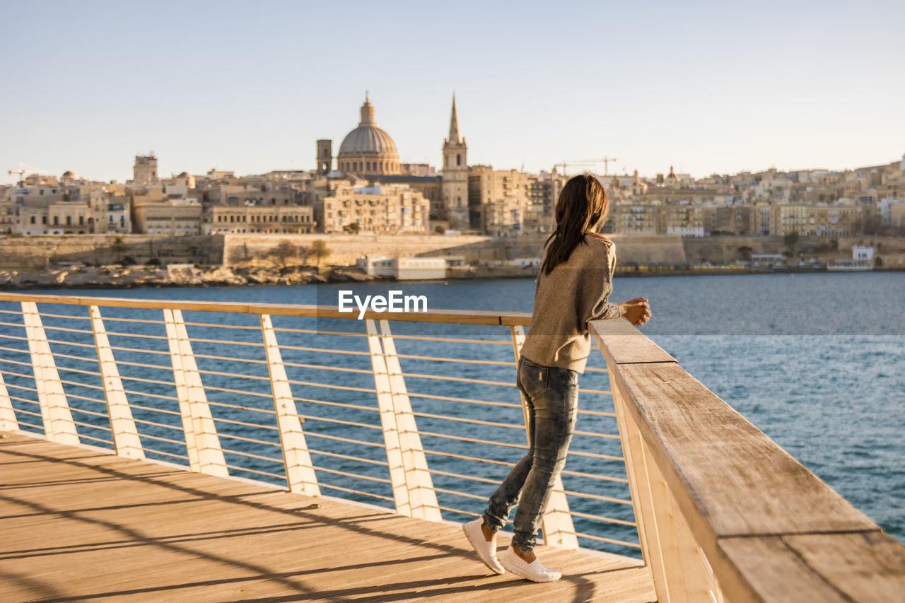 Woman Standing On Promenade By Sea