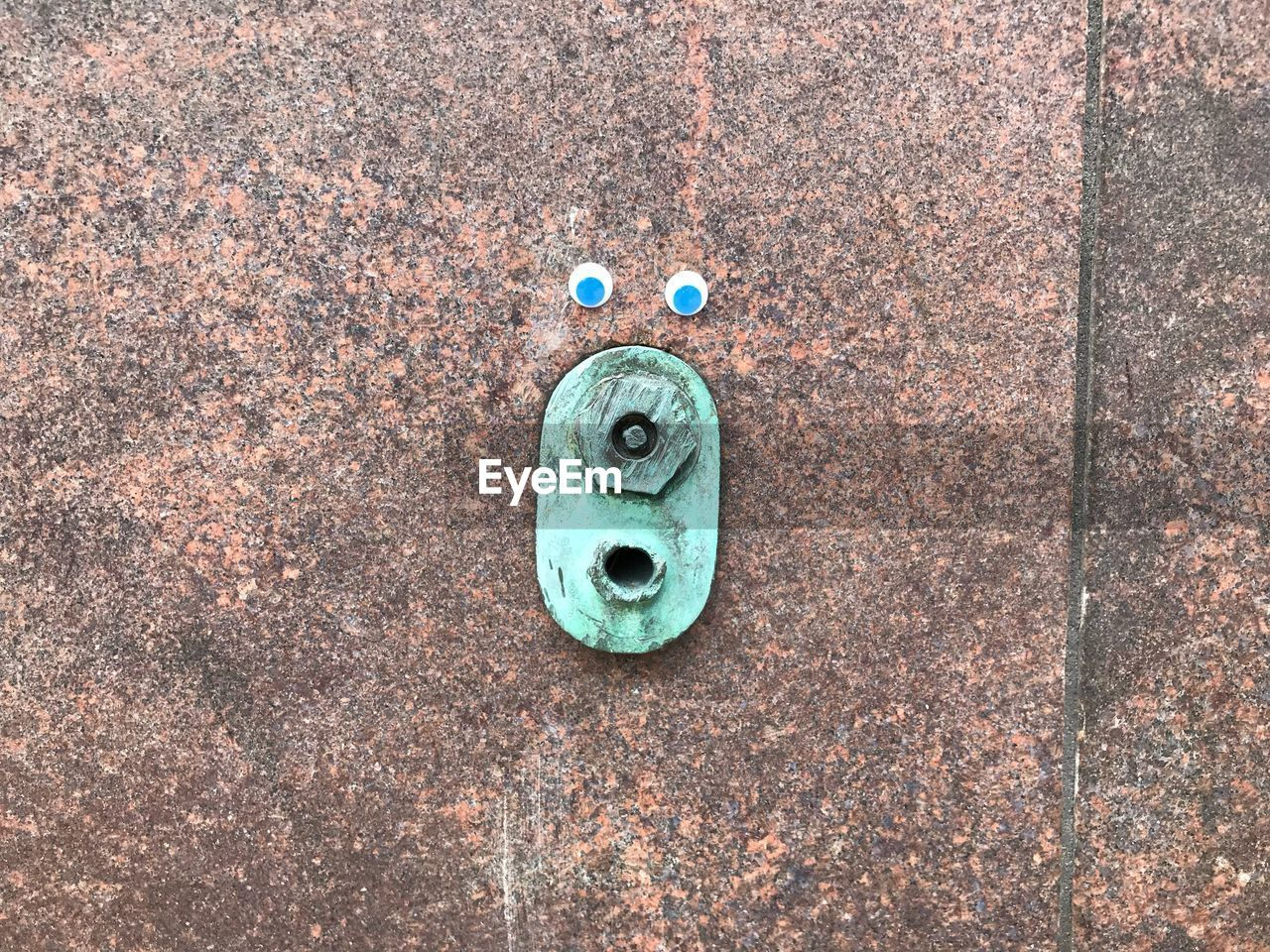Close-Up Of Blue Googly Eyes On Textured Wall