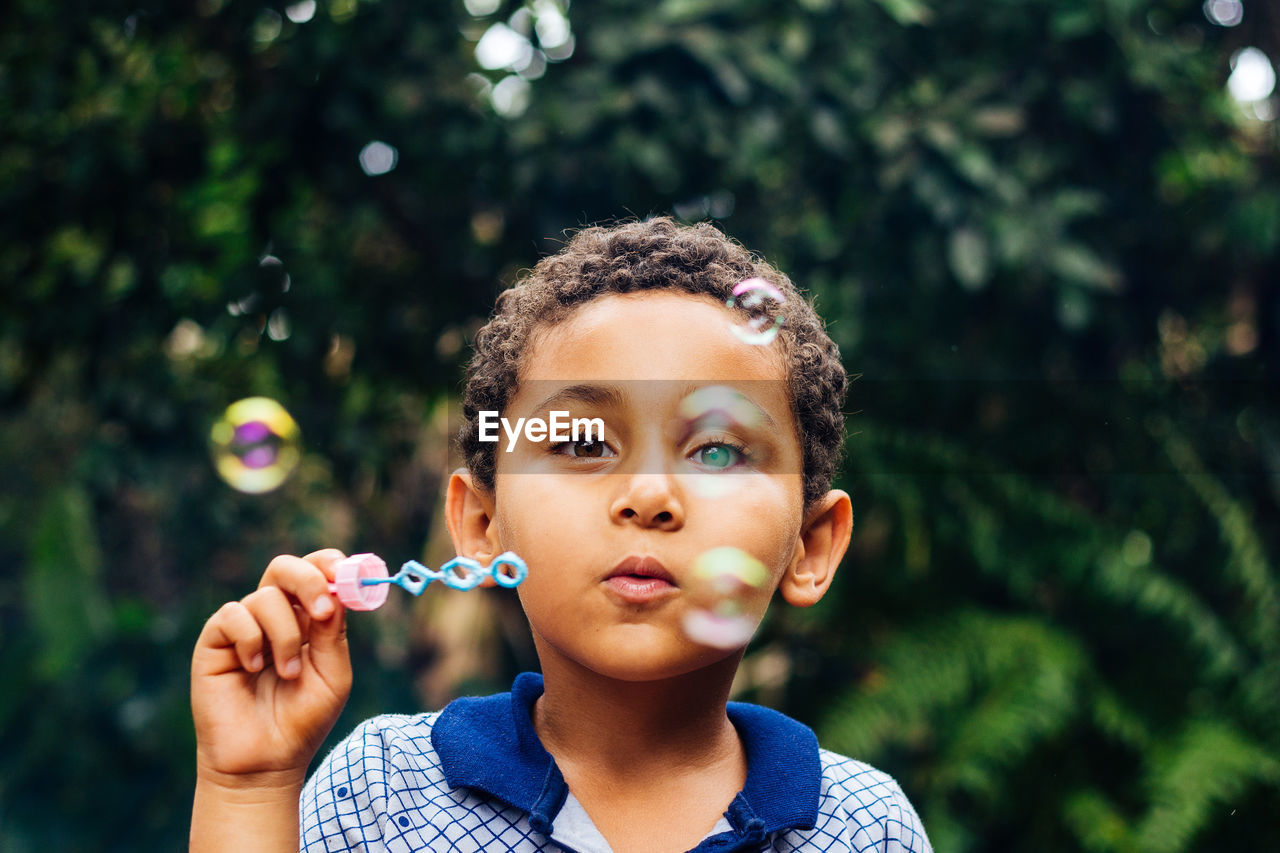 Boy blowing bubbles in park