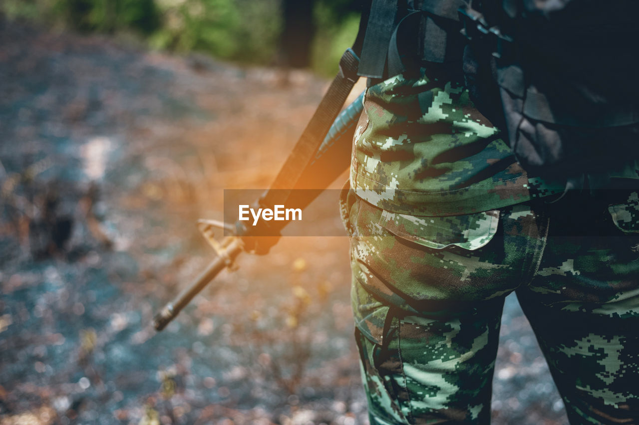 one person, focus on foreground, day, nature, real people, standing, land, outdoors, holding, men, midsection, dirt, weapon, gun, field, low section, human body part, protection, tree